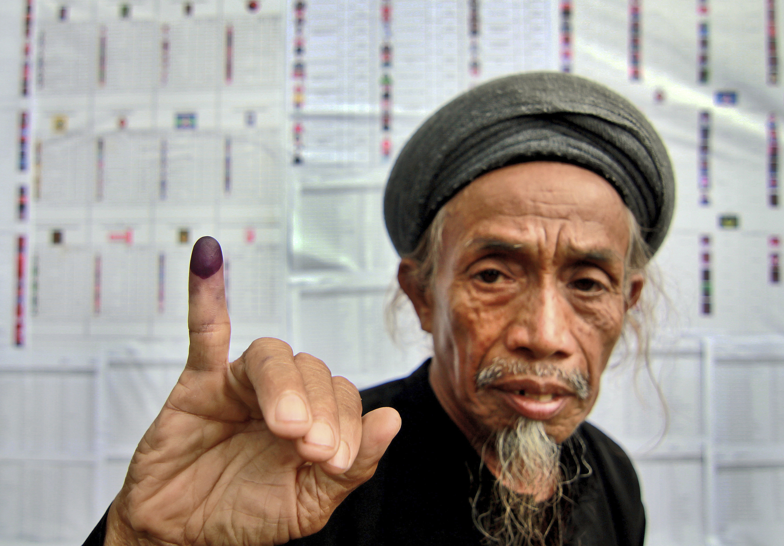 A member of the An-Nadzir Muslim sect shows his inked finger after casting his ballot at a polling station during the Indonesian parliamentary elections in Gowa, South Sulawesi province, on April 9, 2014