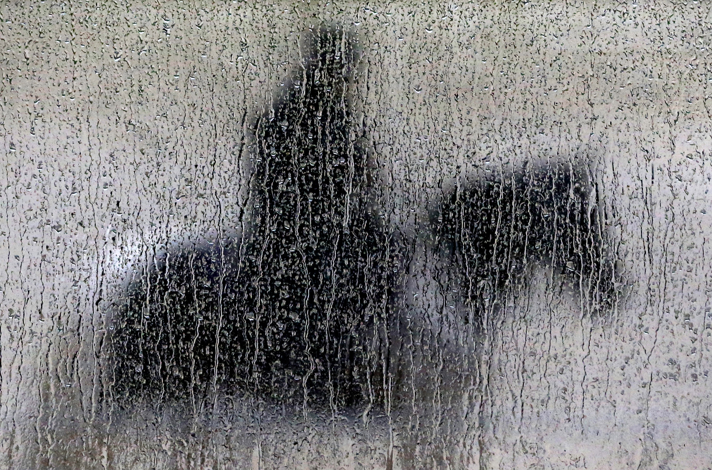 May 16, 2014. Rain runs down a pane of glass as a woman aboard a pony waits to guide a horse off the track during a workout session at Pimlico Race Course in Baltimore,