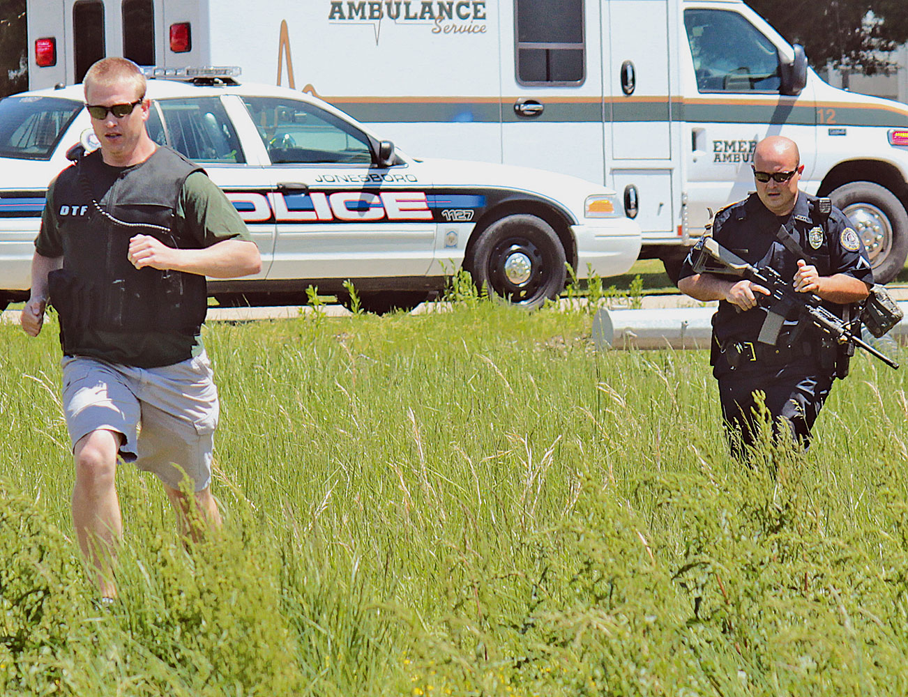 Drug Task Force Detective Josh Talbott, left, and Jonesboro Police Department Patrolman First Class Duane Busby run across a field adjacent to Moore Road while responding to a May 3, 2014 shooting in Jonesboro, Ark.