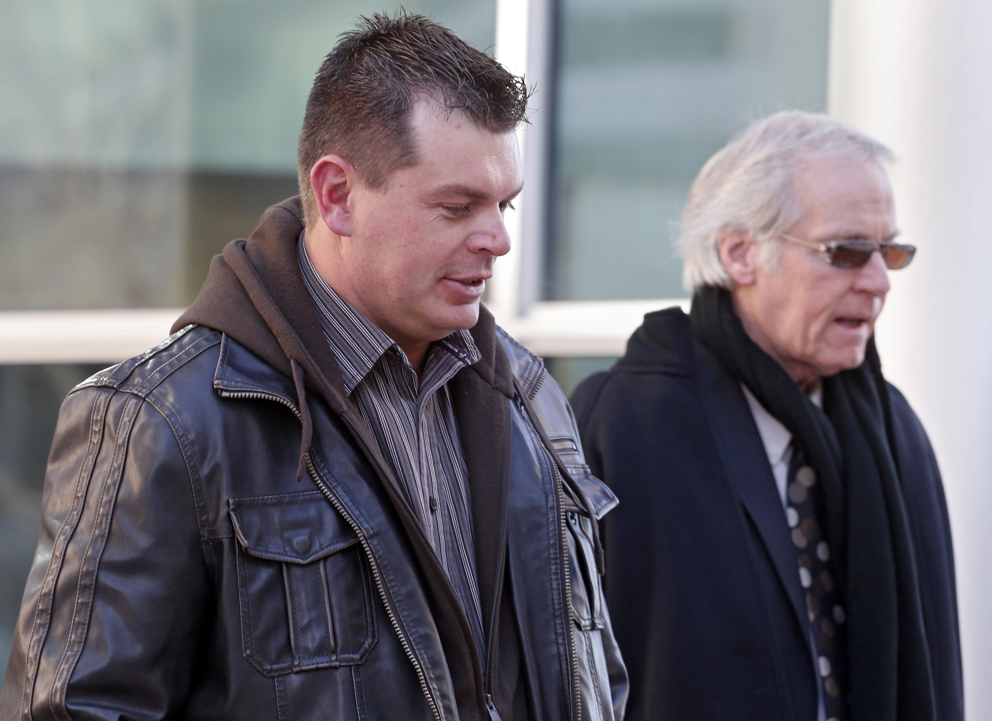 Eric Jensen, left, leaves the federal courthouse in Denver on Jan. 28, 2014, with attorney Forrest Lewis after he and his brother Ryan were sentenced to five years of probation and six months of home detention. The two Colorado cantaloupe farmers, who pleaded guilty to misdemeanor charges stemming from a deadly listeria outbreak in 2011, were also ordered to each pay $150,000 in restitution and perform 100 hours of community service