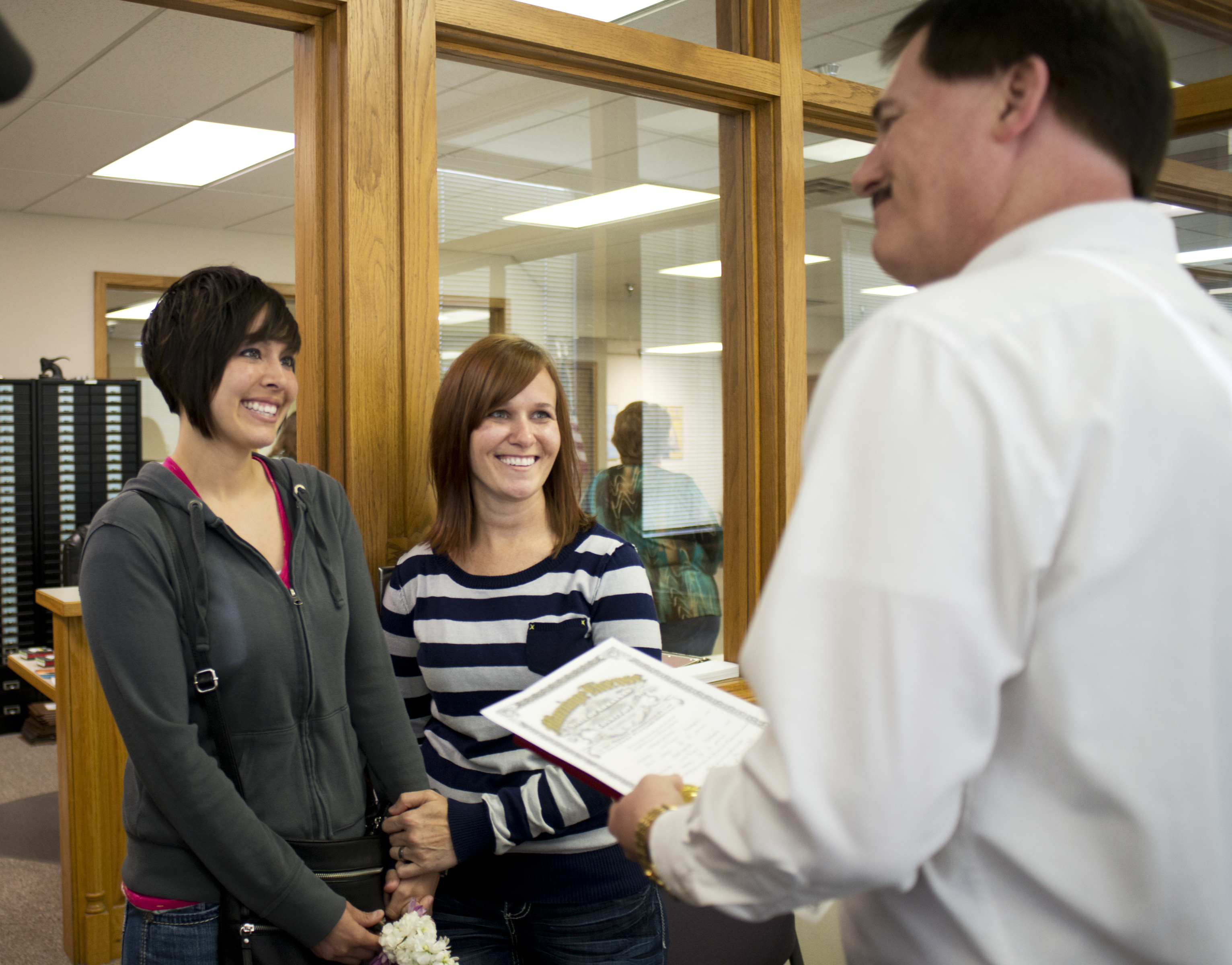 Beth Moore, left, and her partner Abby Hill, center, exchange vows in a marriage ceremony performed by Jeremy Hernandez, right, at the Washington County Courthouse in Fayetteville, Ark., Friday May 16, 2014.