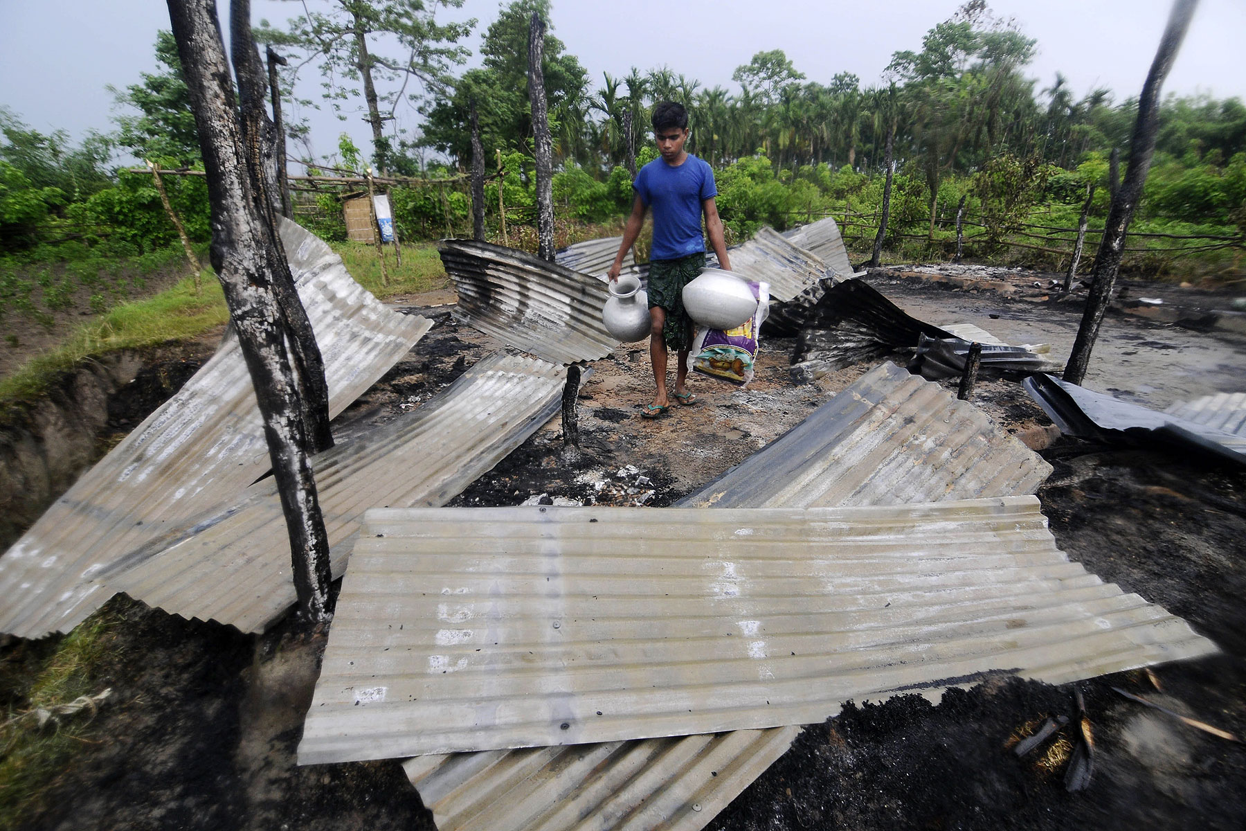 An Indian resident salvages valuables in the remains of his house in the village of Khagrabari, some 200 km west of Guwahati on May 3, 2014, after it was attacked by tribal separatists in India's remote northeastern state of Assam