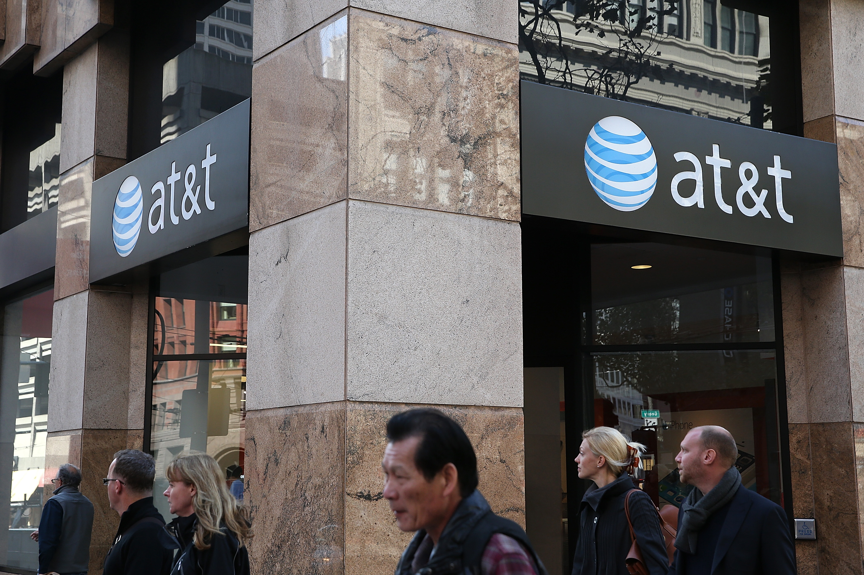 Pedestrians walk by an AT&T store on Oct. 23, 2013 in San Francisco.
