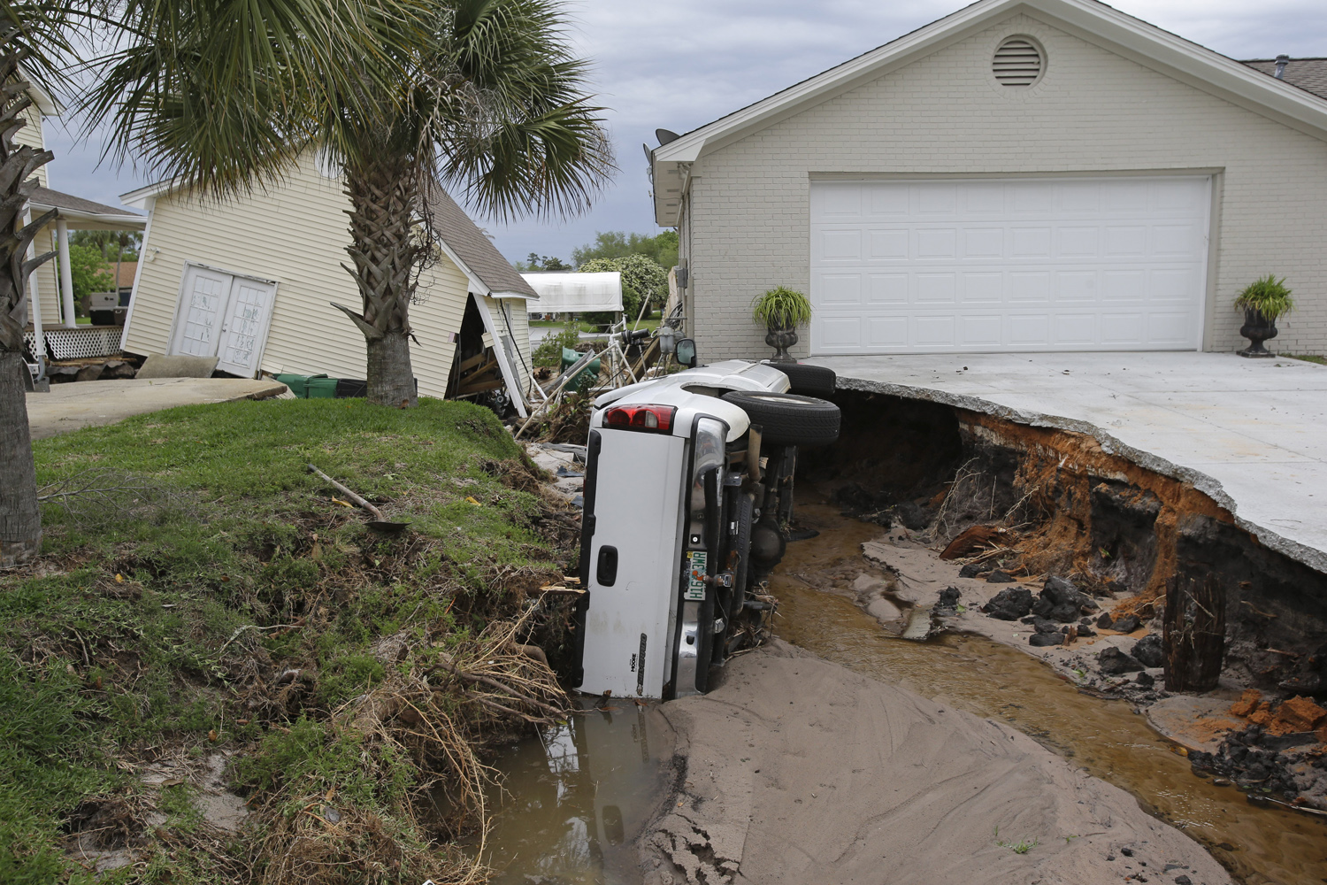 May 1, 2014, A pickup truck remains overturned after flooding collapsed the driveway at this home in the Villa Venyce subdivision,  in Gulf Breeze, Fla.