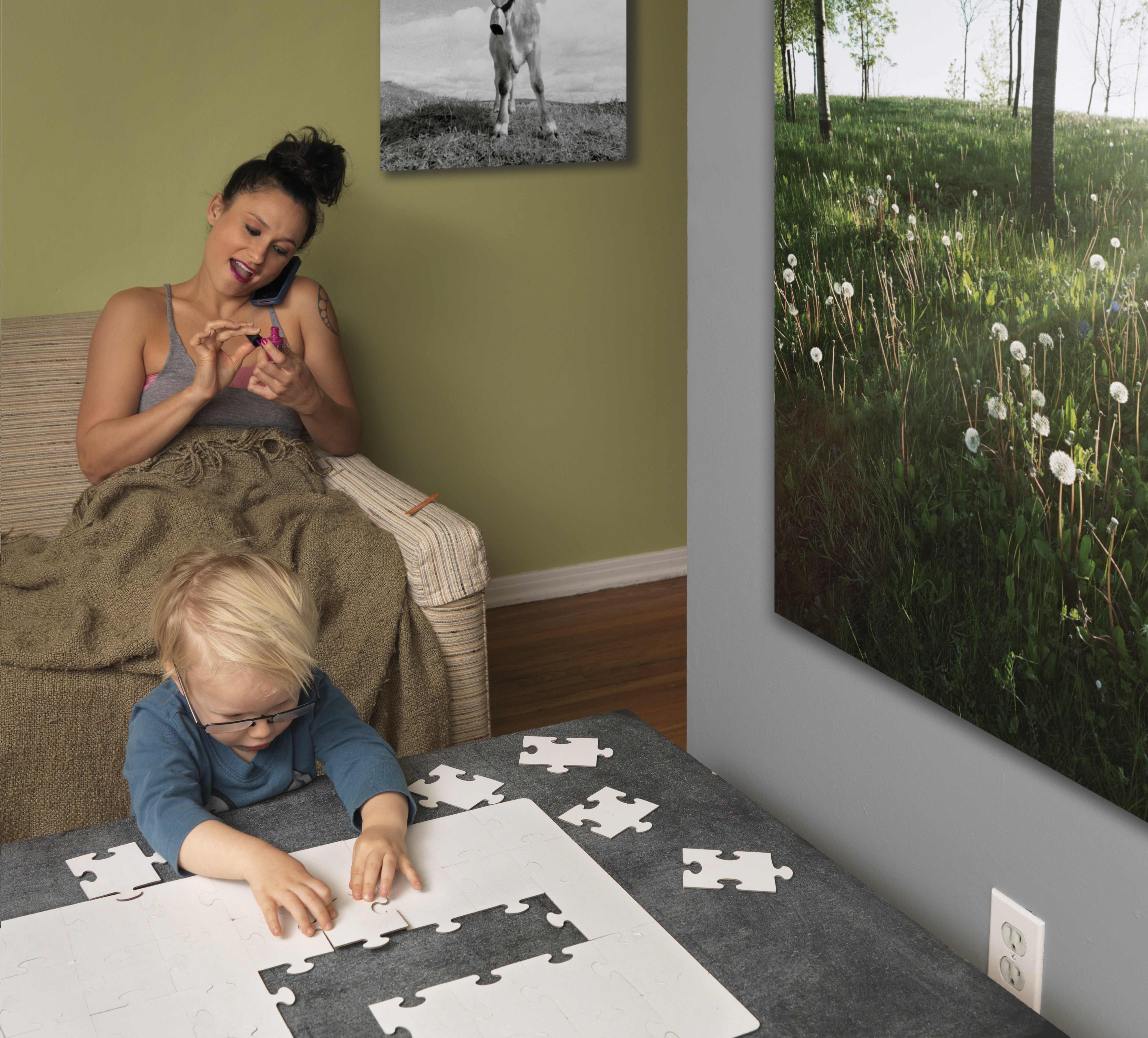 Babysitter with toddler putting together a white jigsaw puzzle