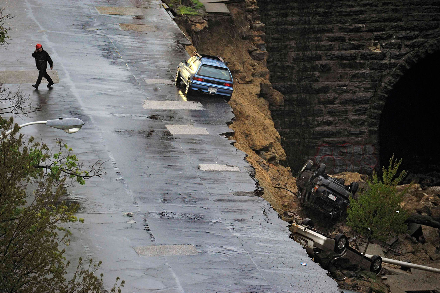 An emergency worker walks on the other side of the street where one car still rests precariously after a retaining wall collapsed beneath a row of vehicles in Baltimore, Maryland, April 30, 2014.
