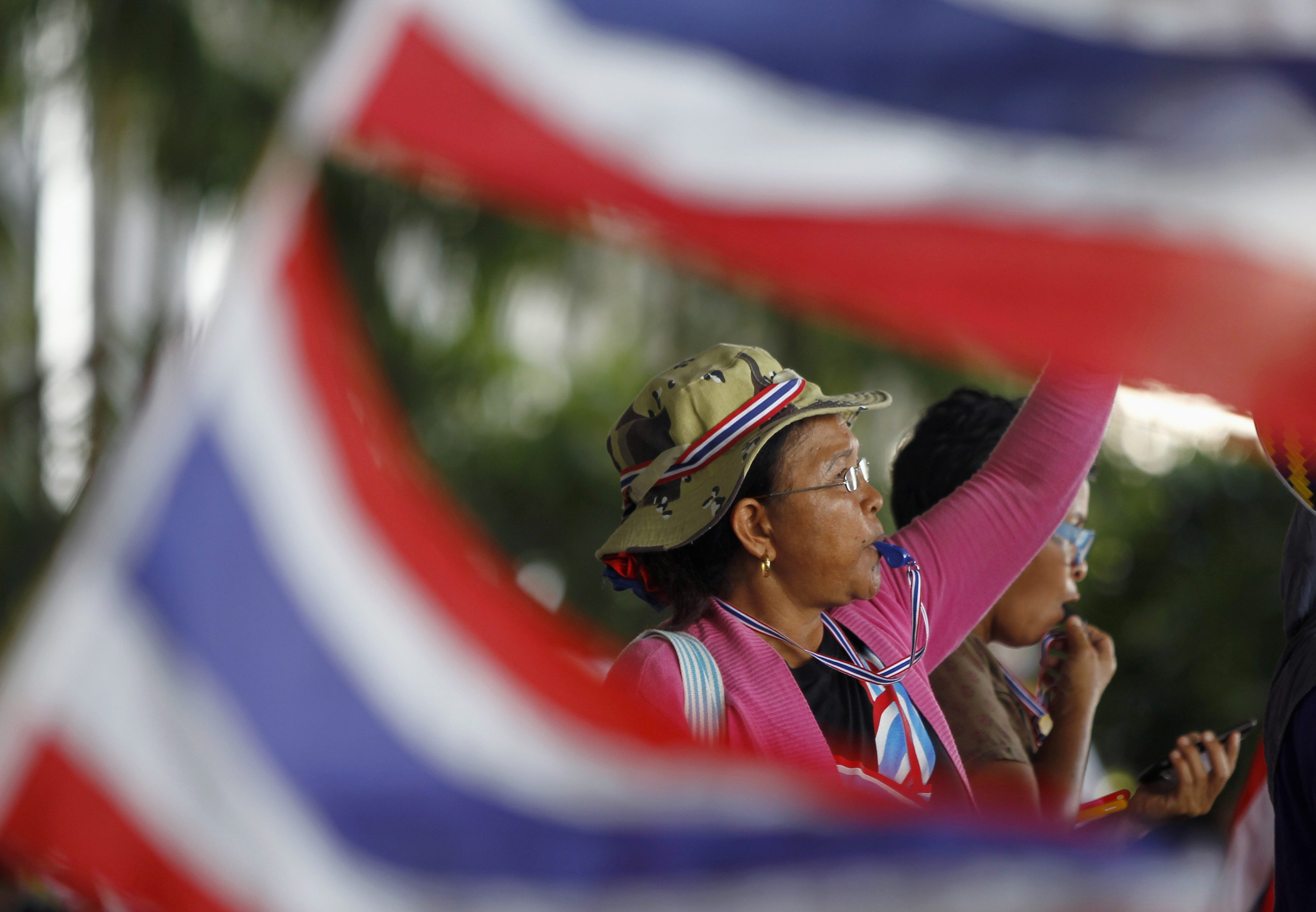 An anti-government protester blows her whistle during a rally outside the office of Election Commission in Bangkok May 15, 2014.