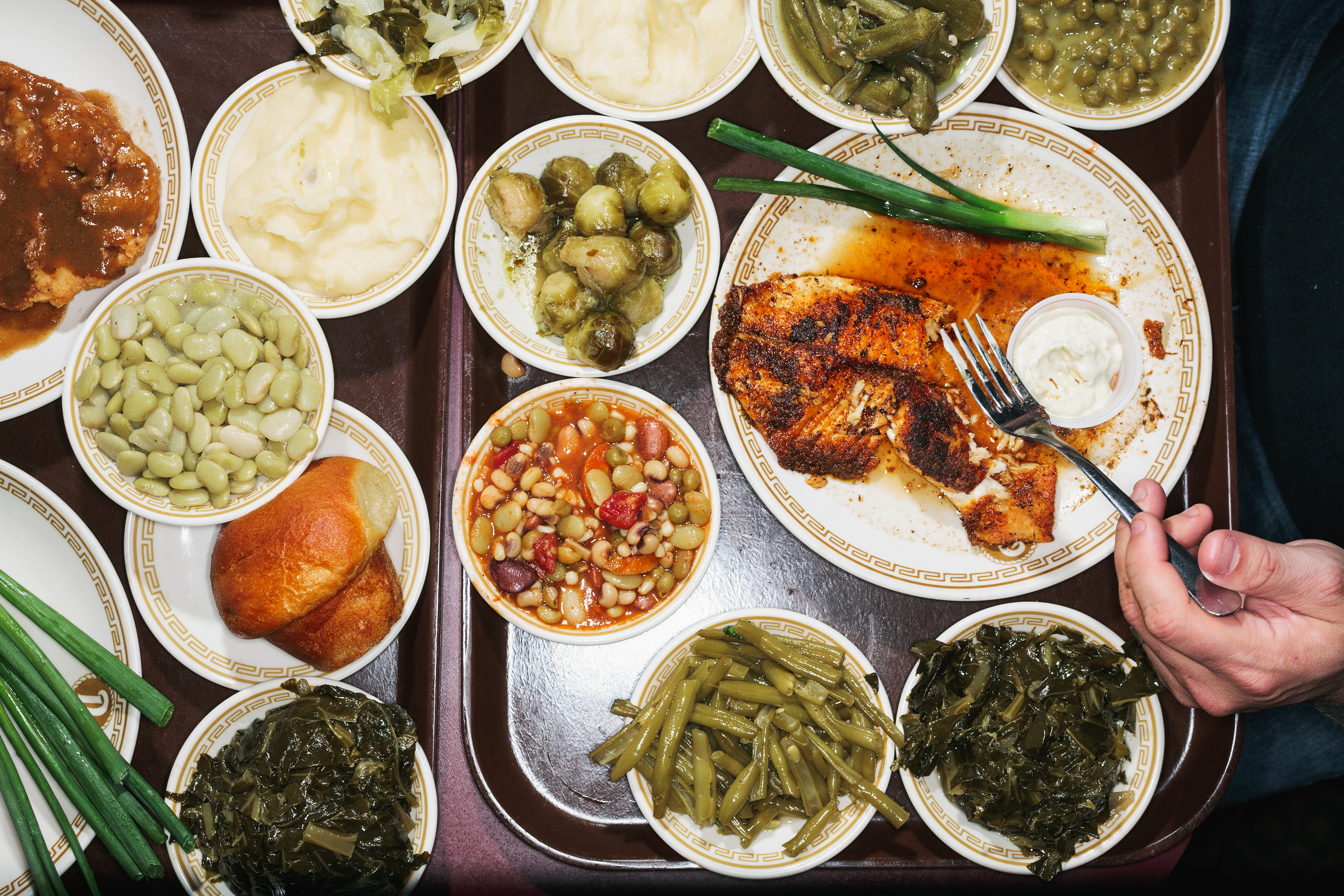 Catfish with a selection of sides (including large lima beans, fresh green beans, collard greens, boiled cabbage, fresh mashed potatoes and brussels sprouts) from the daily cafeteria menu at Niki's West in Birmingham, Ala.