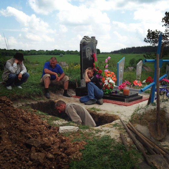 May 15, 2014. Friends and family of Lena Ott, 42, dig her grave in a cemetery in Starovarvarovka, Ukraine.