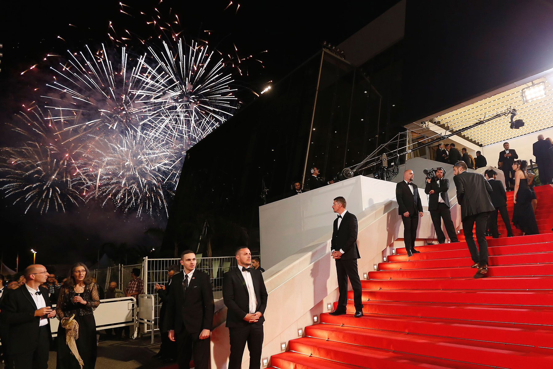 Guests walk on the red carpet during a fireworks show as they arrive for the screening of the film Timbuktu in competition at the 67th Cannes Film Festival in Cannes May 15, 2014