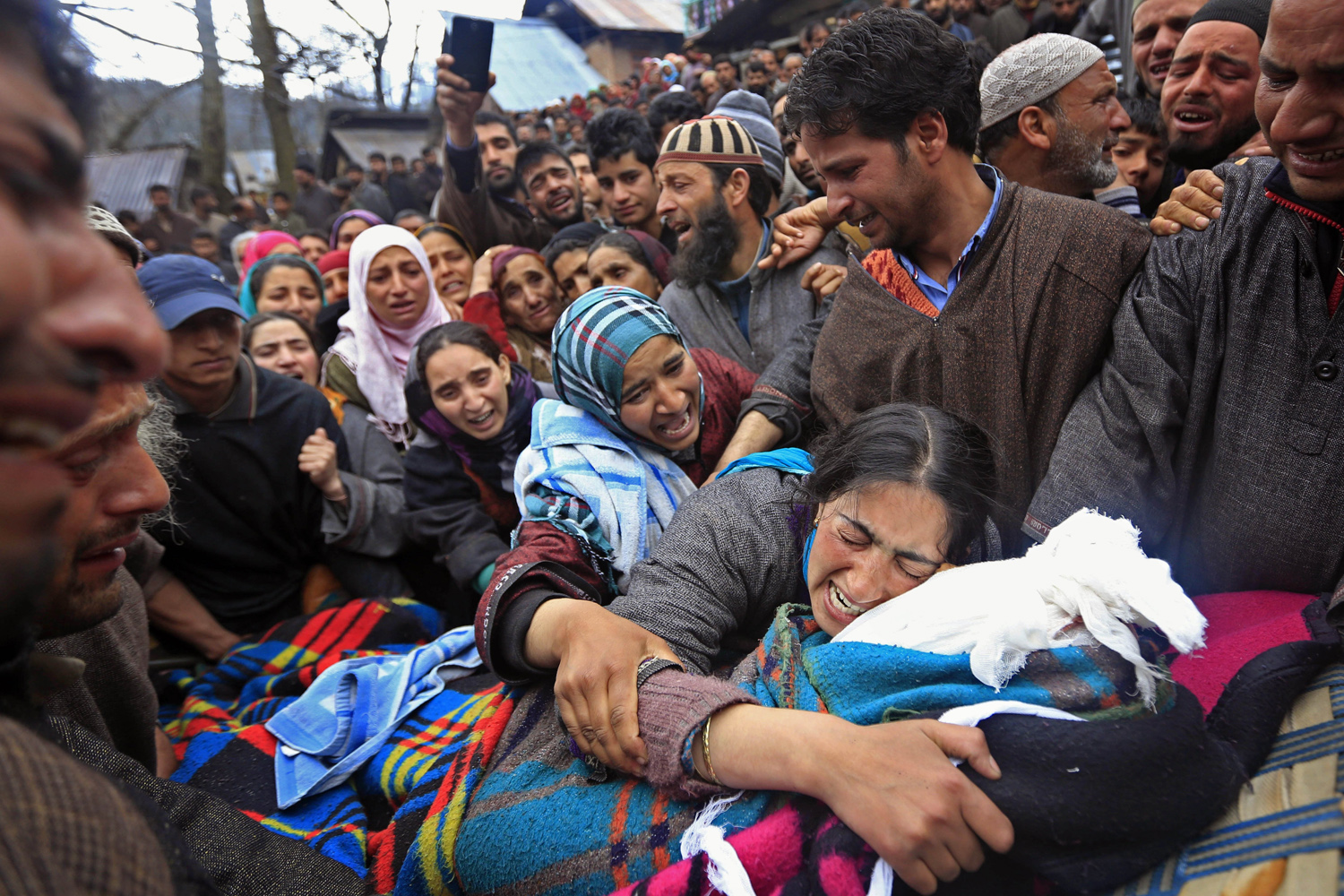 April 25, 2014. Sumaira Wani, wife of Zia-Ul-Haq mourns by the body of her husband during his funeral in Hirpora, north of Srinagar, India.