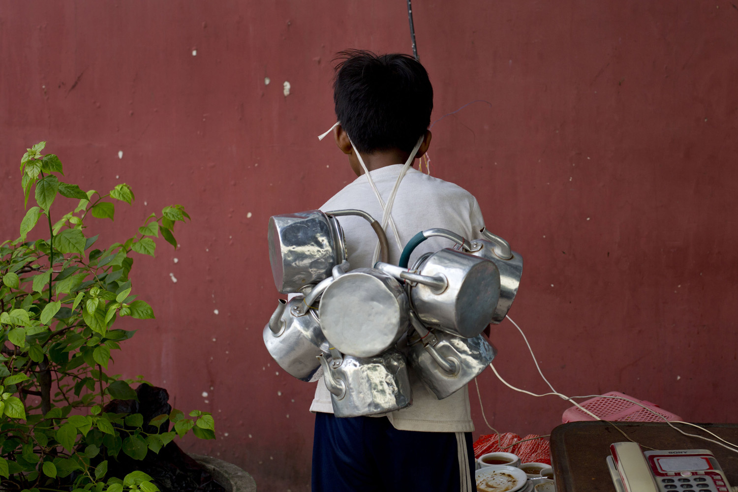May 27, 2014.  A tea delivery boy with empty tea pots attached to a rope hang on to his forehead, collects empty tea cups and tea-pots from an outdoor telephone stand in Yangon, Myanmar.