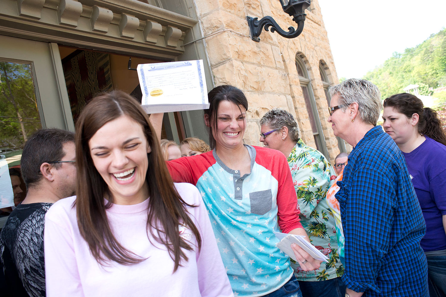 Kristin Seaton, center, of Jacksonville, Ark., holds up her marriage license as she leaves the Carroll County Courthouse in Eureka Springs, Ark., with her partner, Jennifer Rambo, left, of Fort Smith, Ark. May 10, 2014, in Eureka Springs, Ark.