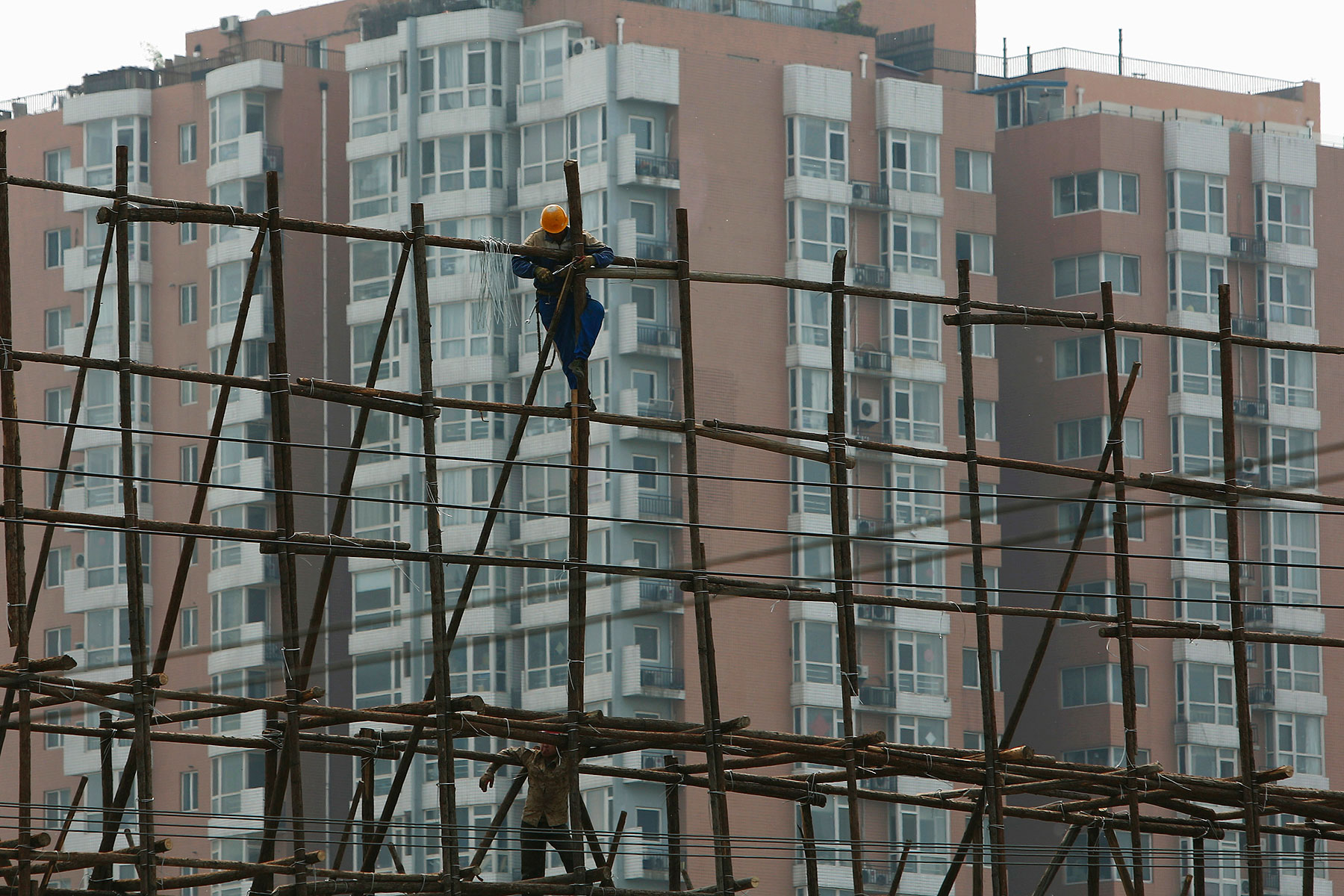 A laborer works on the scaffolding of a construction site for a new residential building in Beijing on May 8, 2014