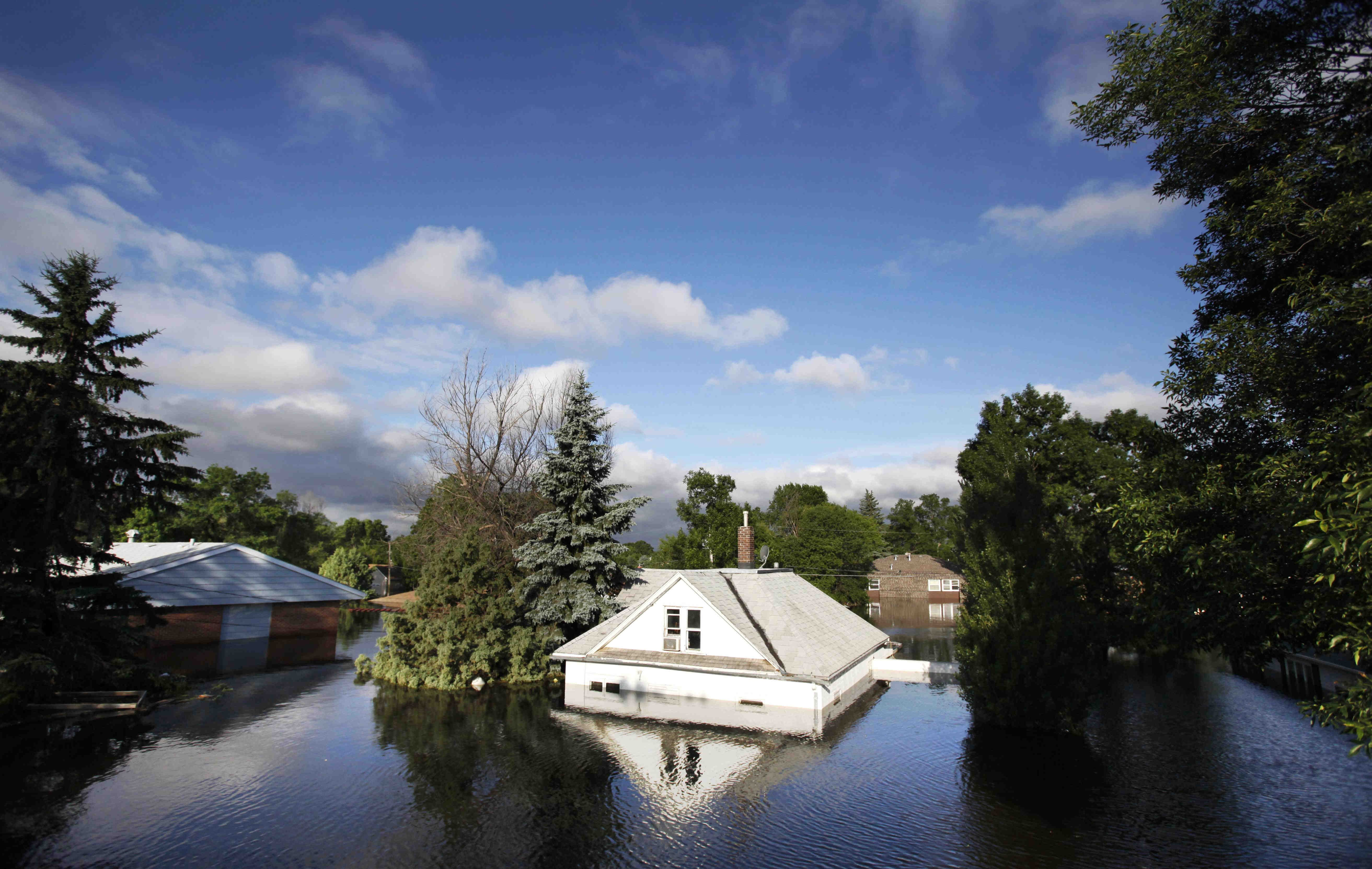 Floodwaters from the Souris River surround homes near Minot State University in Minot, N.D. in this June 27, 2011 file photo.