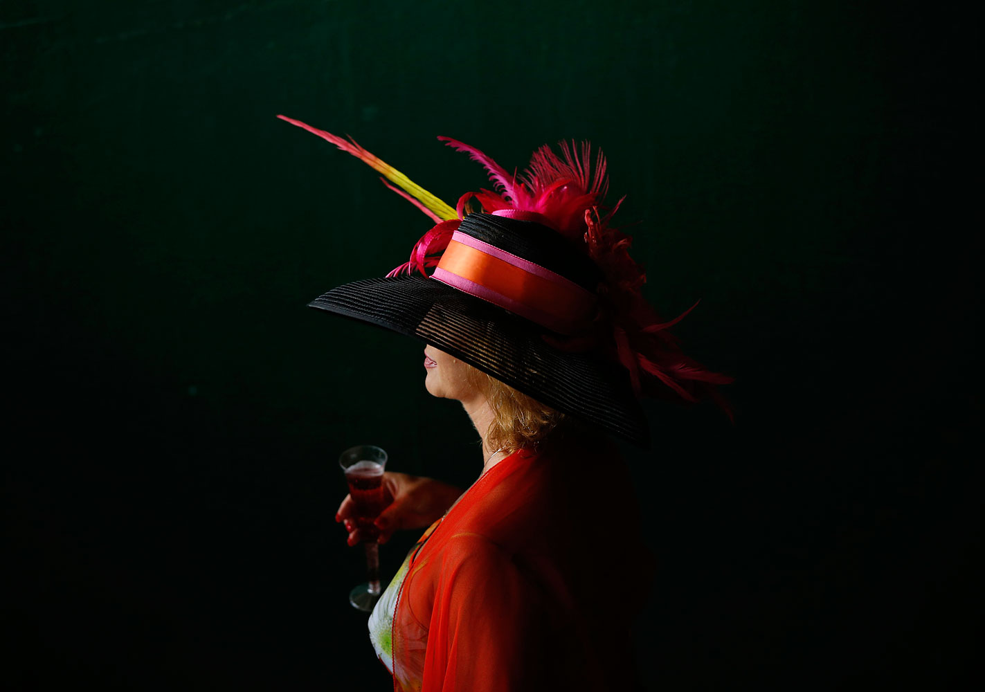 A woman makes her way to the track in a stunning black and red Derby hat.