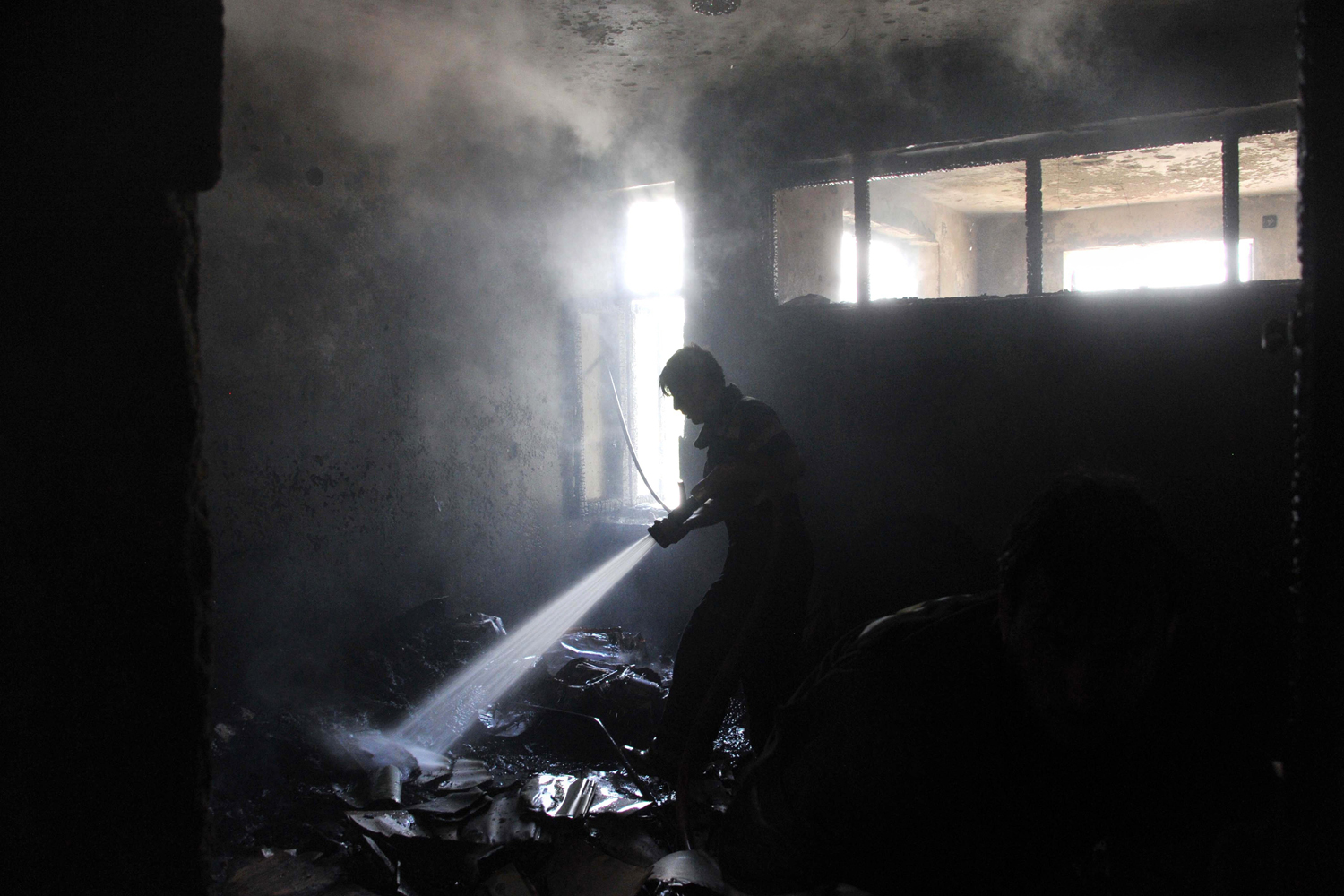 May 12, 2014. An Afghan firefighter extinguishes a fire at the site of a suicide attack in Jalalabad province.