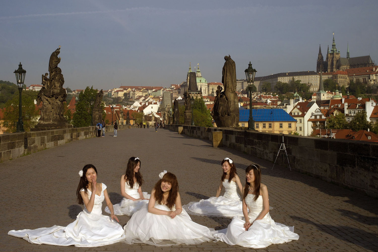 Newly married brides wait for their photo to be taken on the landmark Charles Bridge in Prague,  Czech Republic, on May 6, 2014.