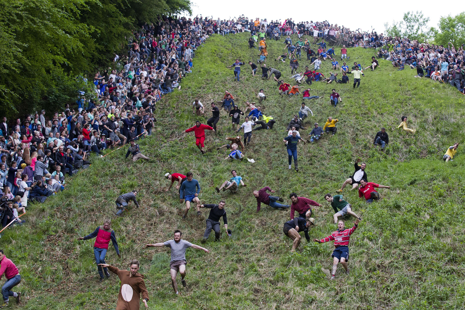 May 26, 2014. Competitors tumble down Coopers Hill in pursuit of a round Double Gloucester cheese during the annual cheese rolling and wake near the village of Brockworth near Gloucester in western England.