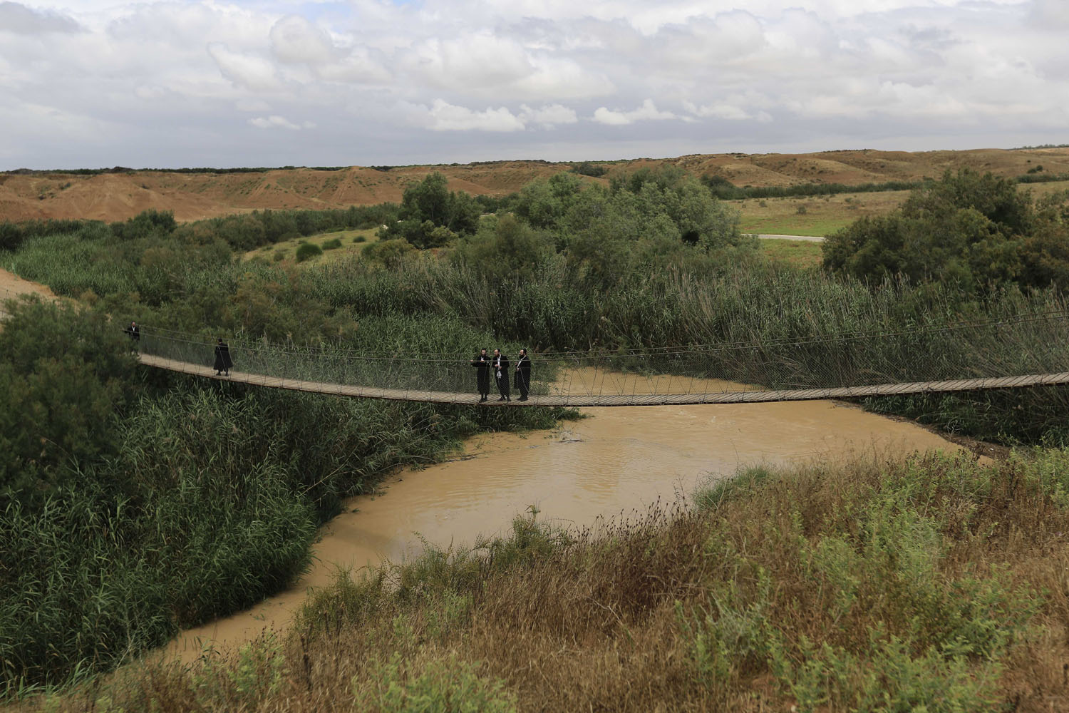 May 8, 2014. Ultra-Orthodox Jewish men walk on the rope bridge over the flooded Besor stream in the southern Negev desert, Israel,