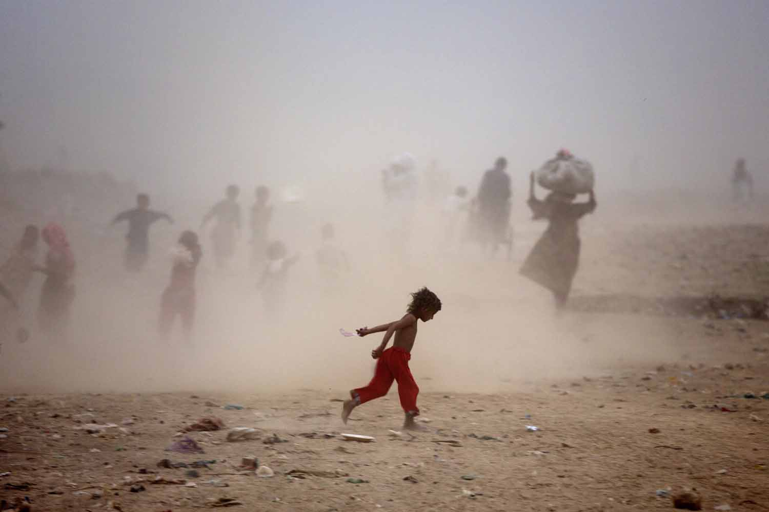 May 29, 2014. Pakistanis run as they get caught in a sand storm on the outskirts of Islamabad, Pakistan.