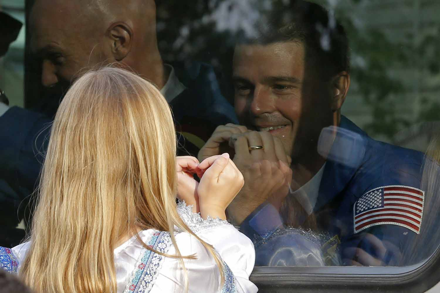 May 28, 2014. NASA astronaut Reid Wiseman, crew member of the mission to the International Space Station, ISS, gestures with his daughter, from a bus as they leave from a hotel prior the launch of Soyuz-FG rocket at the Russian leased Baikonur cosmodrome in Kazakhstan.