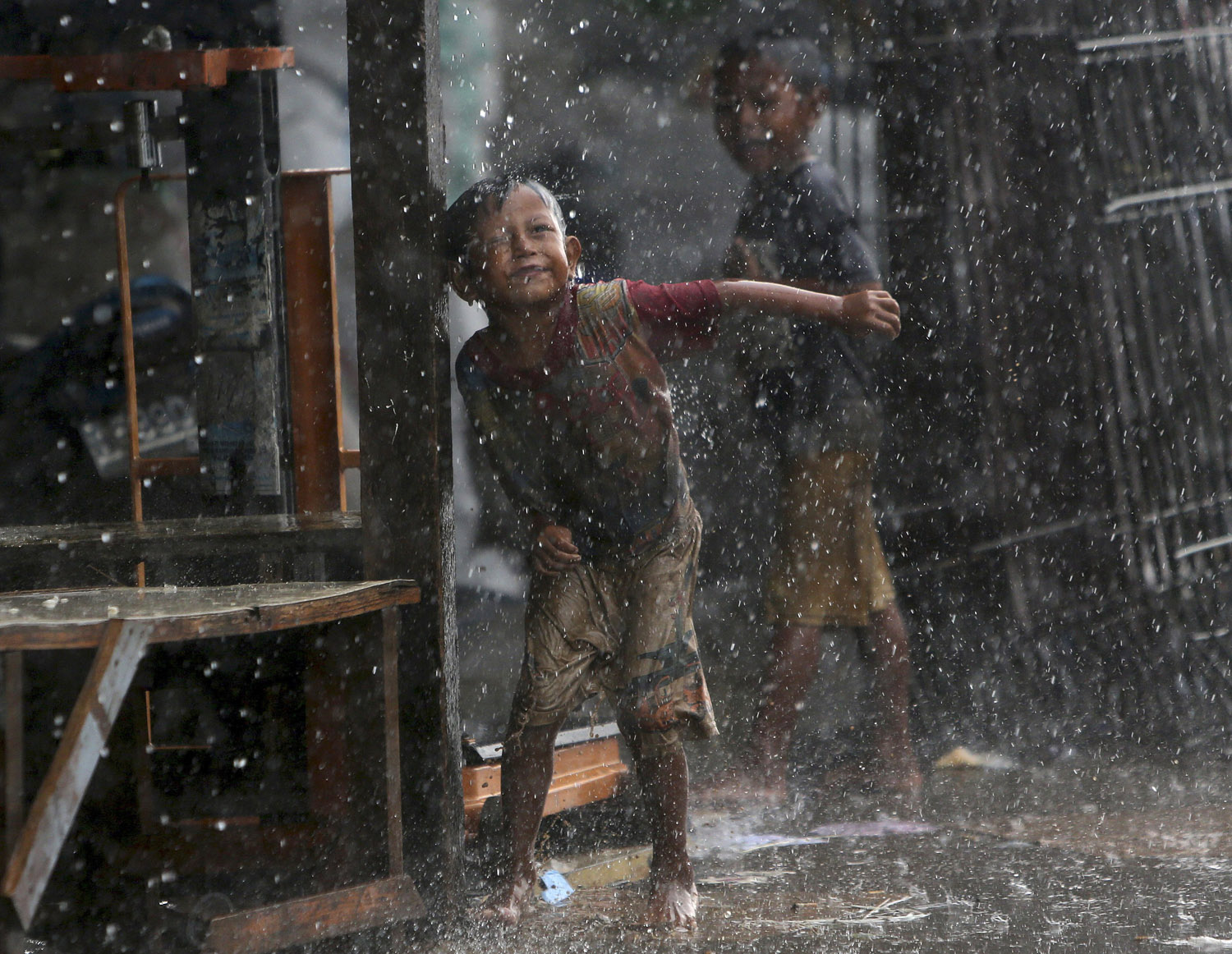 Indonesian children play in the rain during a heavy downpour in Jakarta on May 28, 2014.