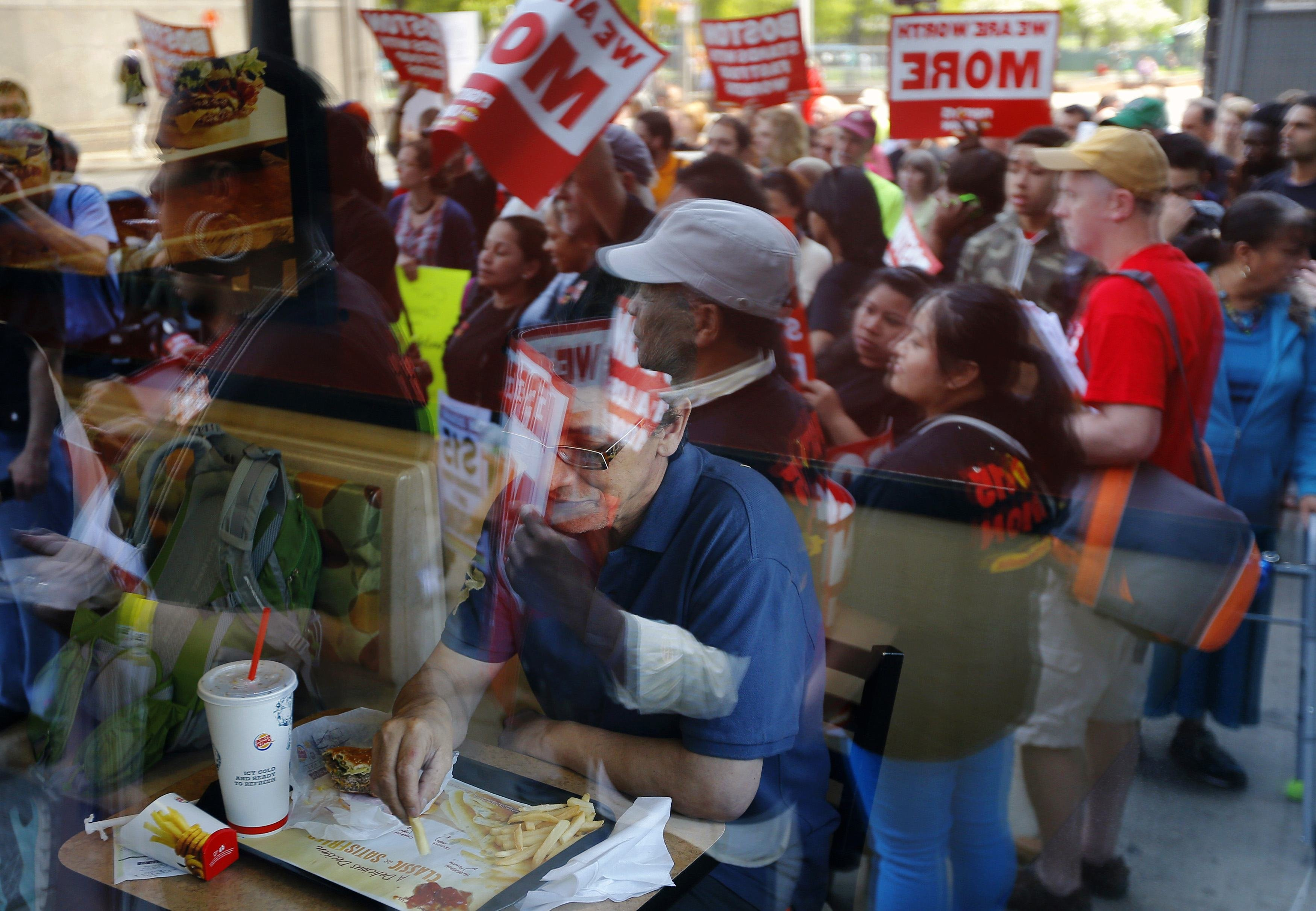 <b>Boston:</b> Demonstrators are reflected in the window as a man eats inside a Burger King restaurant on May 15, 2014.