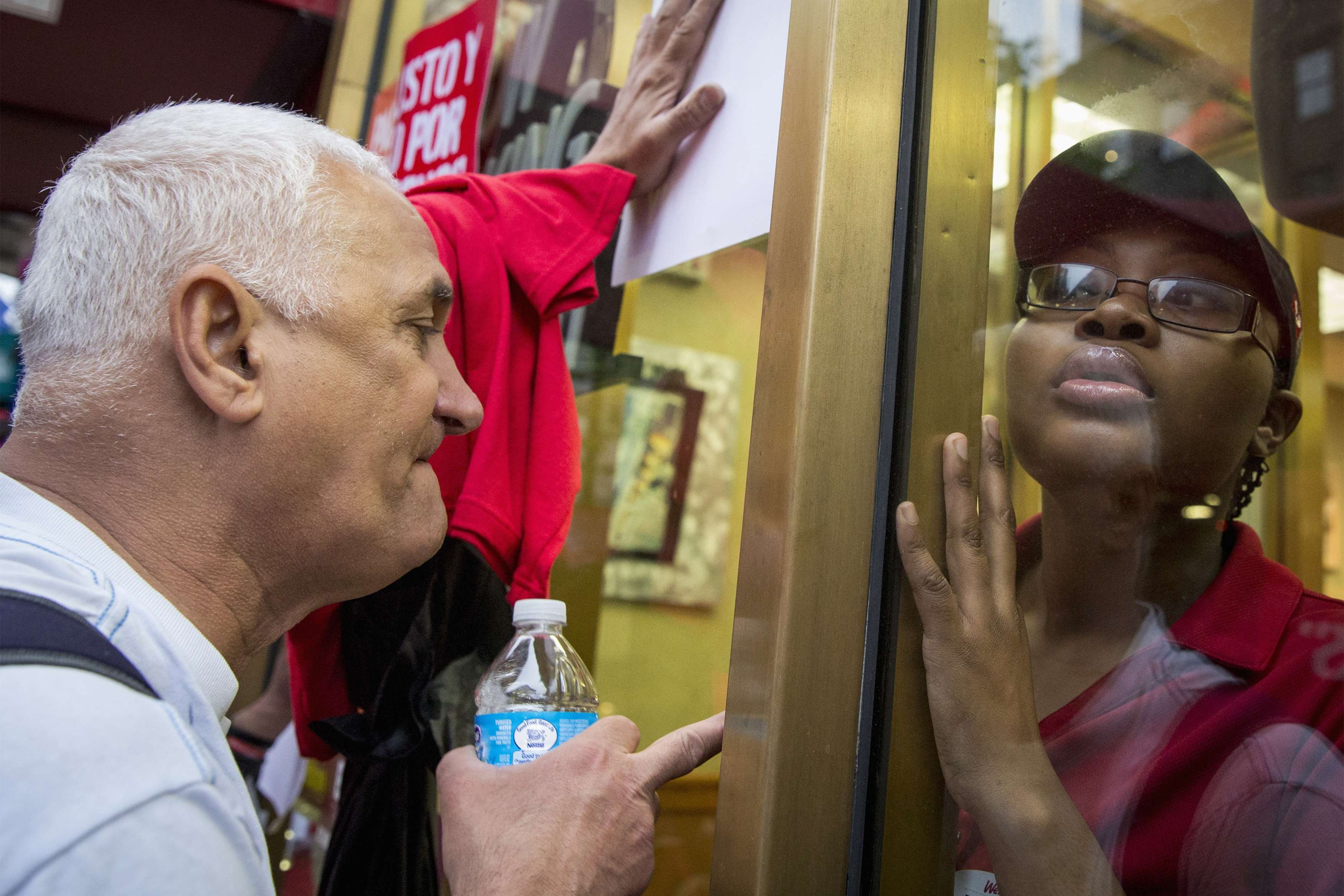 <b>New York:</b>  A Wendy's restaurant worker looks out at a fair wage demonstration as it passes by on May 15, 2014.