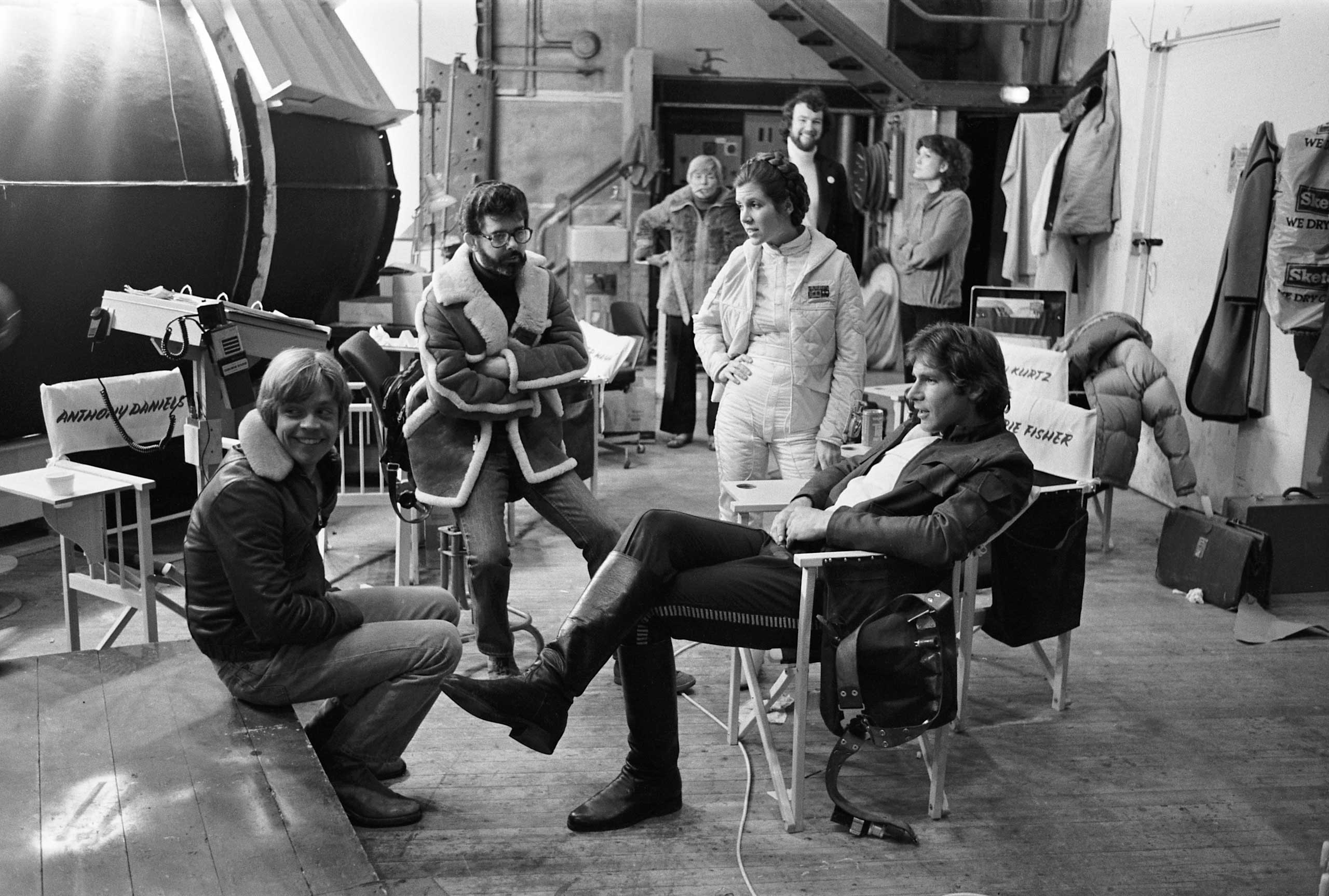 Mark Hamill, Carrie Fisher (Princess Leia) and Harrison Ford (Han Solo) sit around Lucas on the set of <i>The Empire Strikes Back</i>.