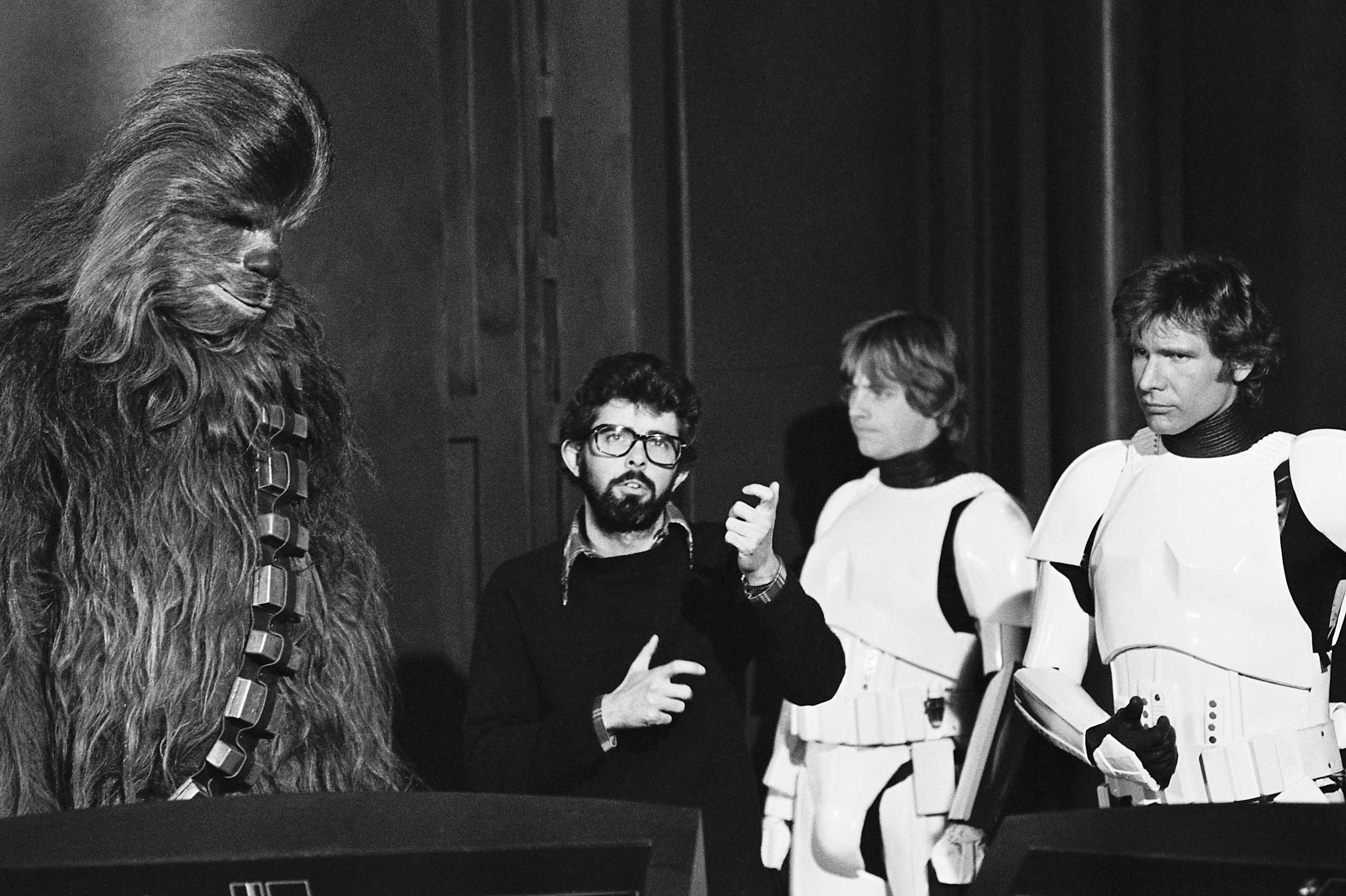 Lucas with Peter Mayhew (Chewbacca), along with Hamill and Ford on the set of Episode IV.