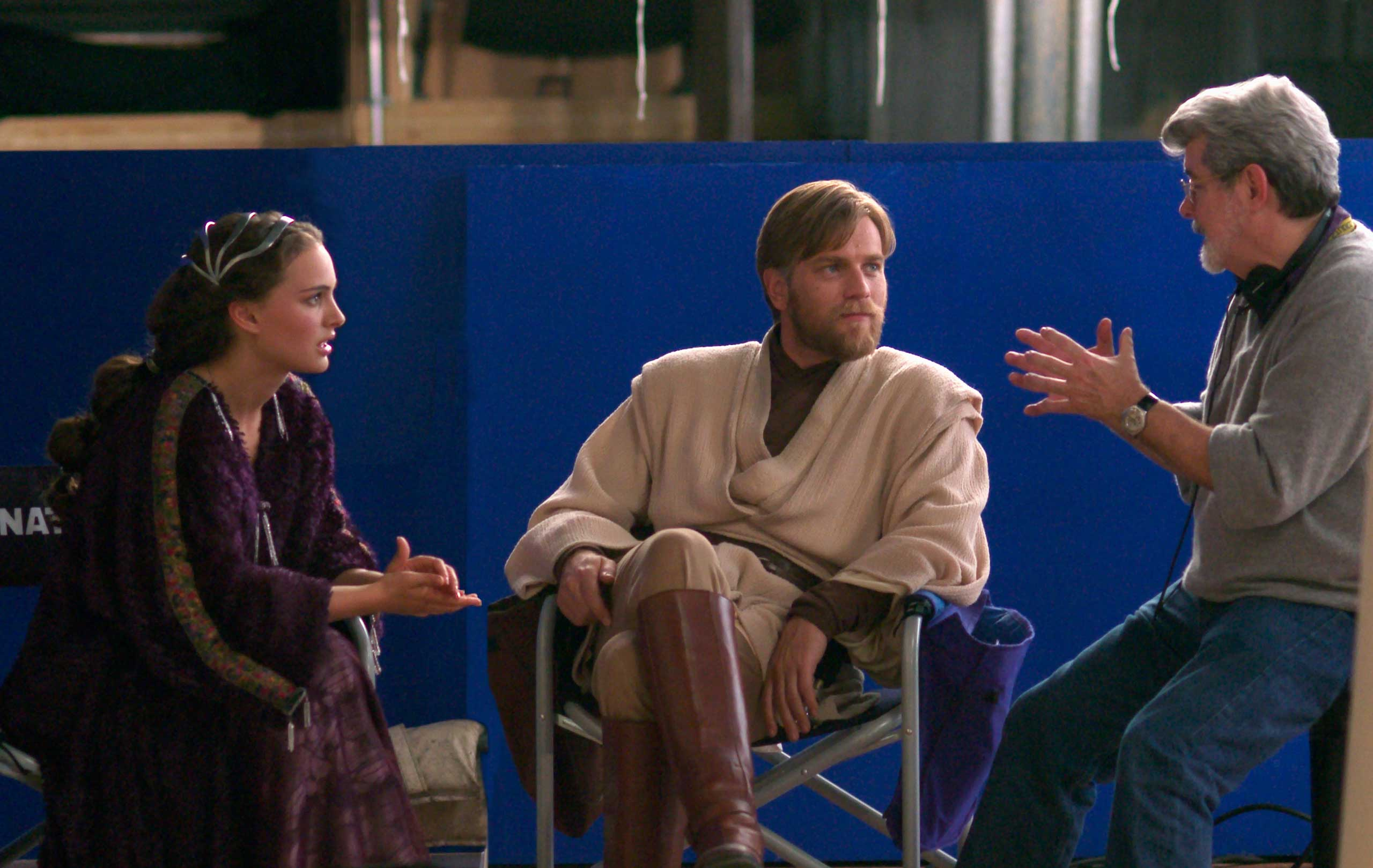 Natalie Portman (Queen Amidala) and Ewan McGregor (Obi-Wan Kenobi) listen to Lucas' directions on the set of <i>Star Wars: Episode III - Revenge of the Sith</i>.