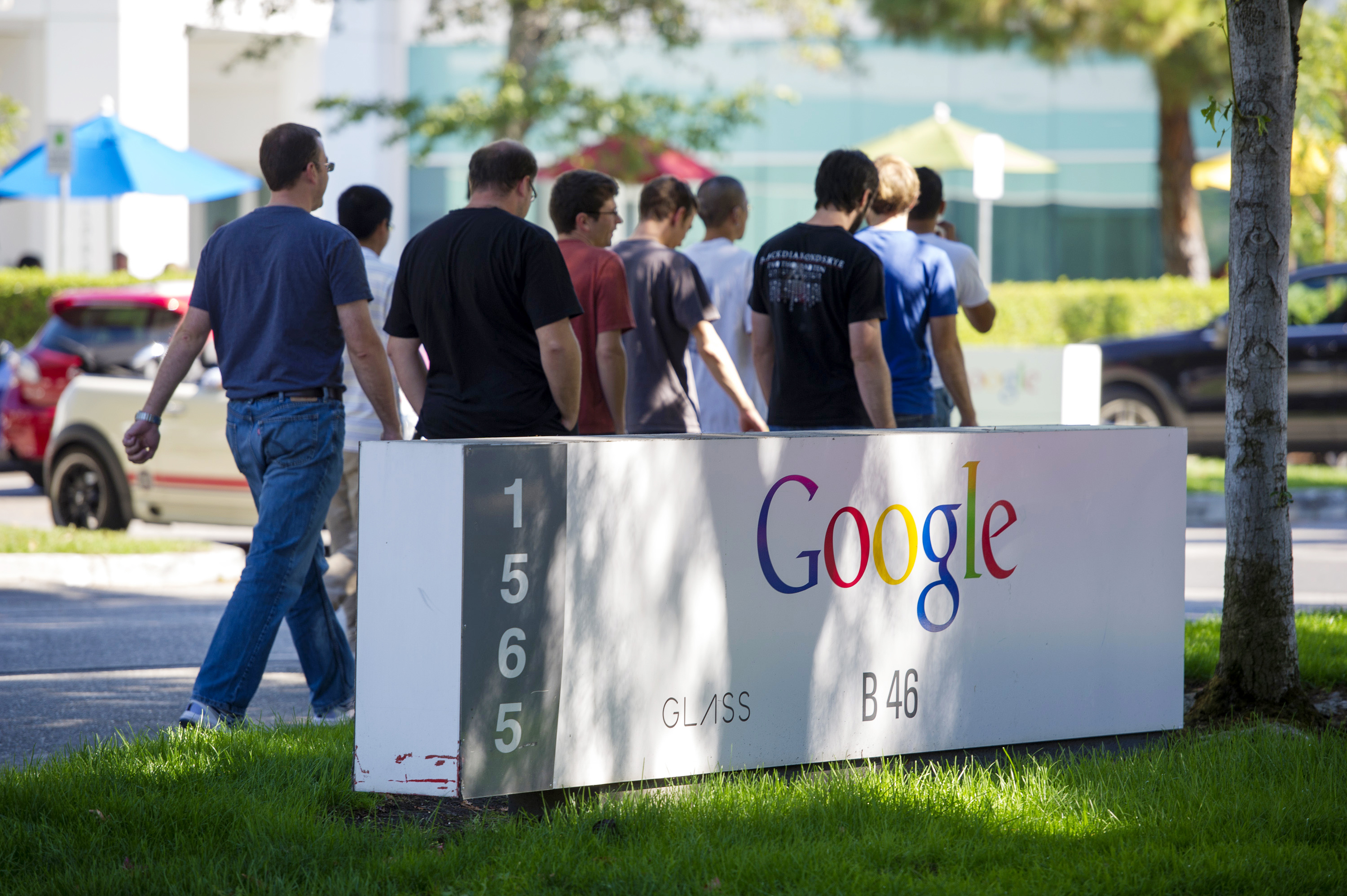 Pedestrians walk past Google Inc. signage displayed in front of the company's headquarters in Mountain View, Calif. on Sept. 27, 2013.