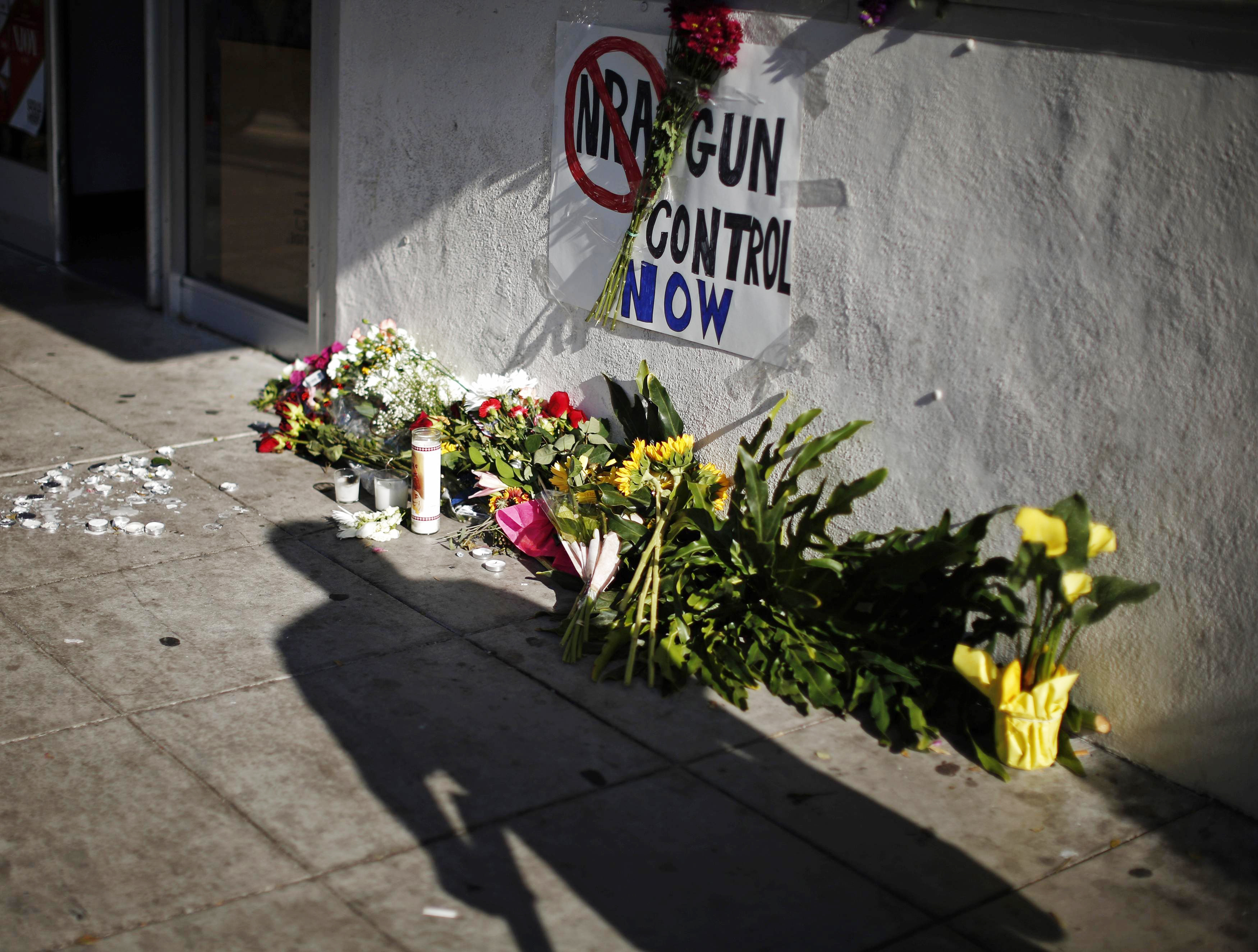 A sign advocating gun control is seen on a makeshift memorial for 20-year-old UCSB student Christopher Michael-Martinez outside a deli that was one of nine crime scenes after a series of drive-by shootings that left 7 people dead in the Isla Vista neighborhood of Santa Barbara, Calif. May 25, 2014.