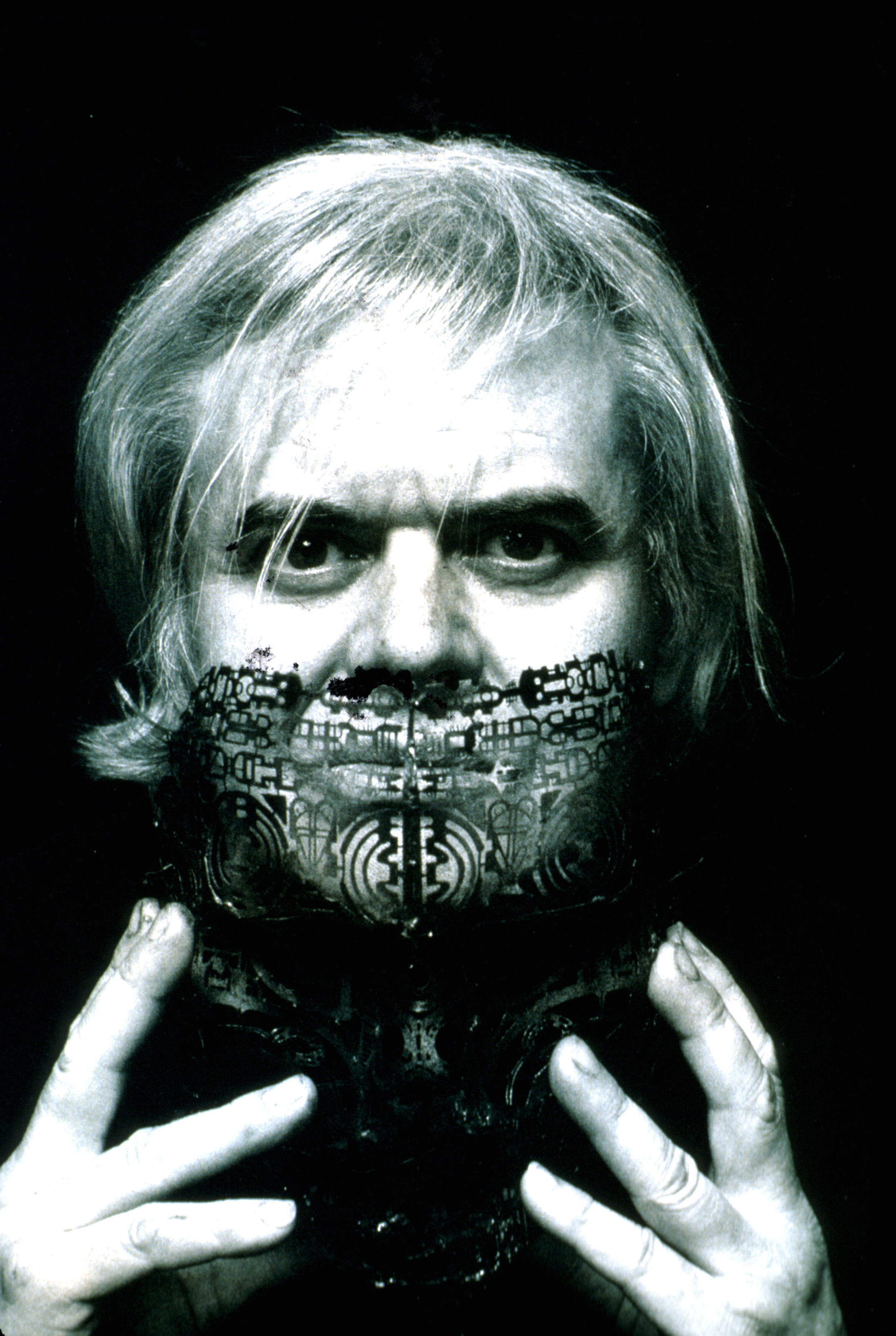 Visual artist H. R. Giger taking off face mask.
