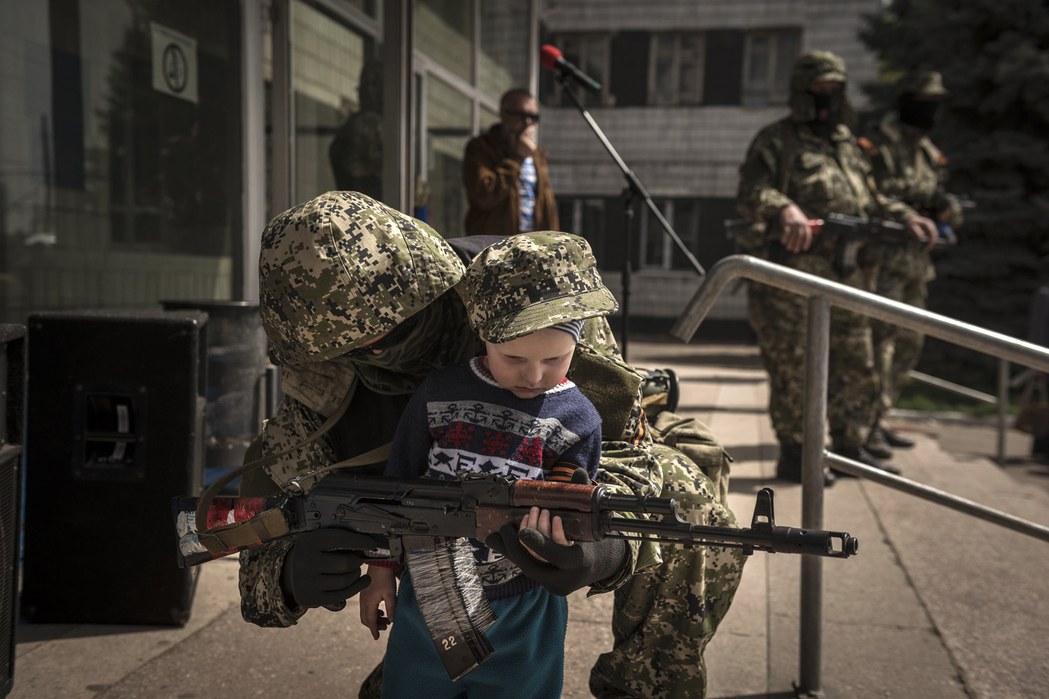 Apr. 28, 2014. A pro-Russia militia member standing guard outside a seized government building allows a child to partially hold his gun, in Konstantinovka, Ukraine,