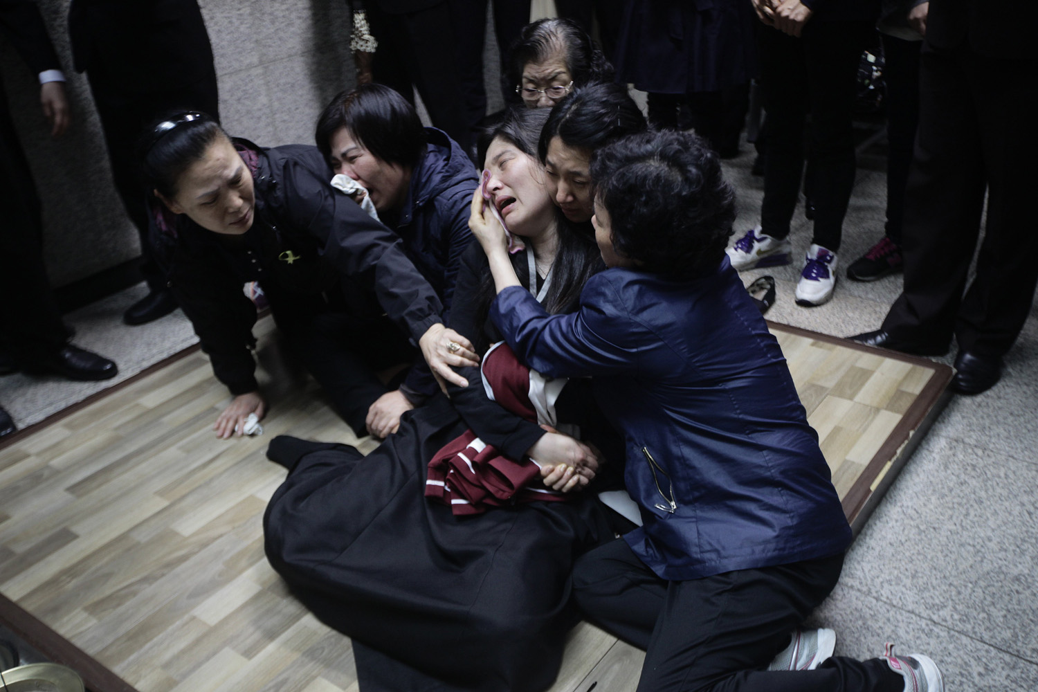 April 27, 2014. Eom Ji-young, center, mother of Park Yae-ji, a 16-year-old victim of the sunken Sewol ferry accident, collapses in grief as her daughter's remains enter the kiln at a crematorium in Suwon, South Korea,