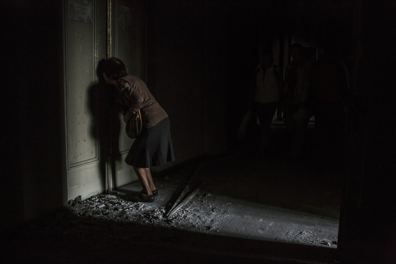 May 4, 2014. A woman tries to look through a hole in a door during a visit to the trade union building that was set on fire, contributing to 46 deaths during clashes in Odessa, Ukraine.