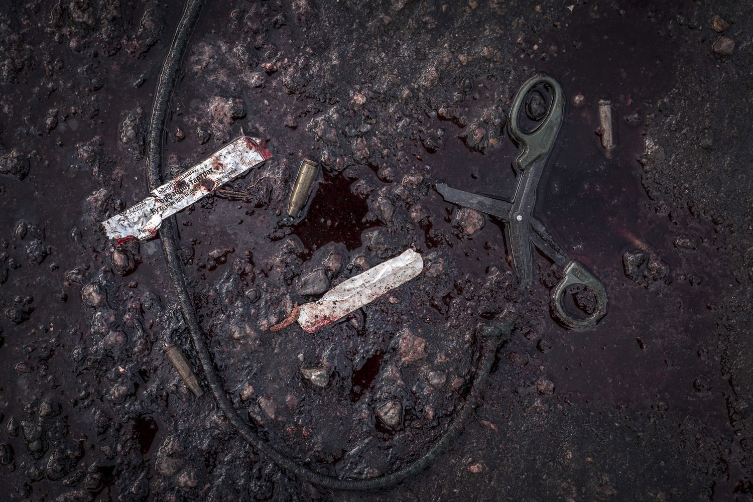 May 5, 2014. Bullet casings, scissors and the wrapper to a tourniquet lie in a puddle of blood on the outskirts of Slovyansk, eastern Ukraine.