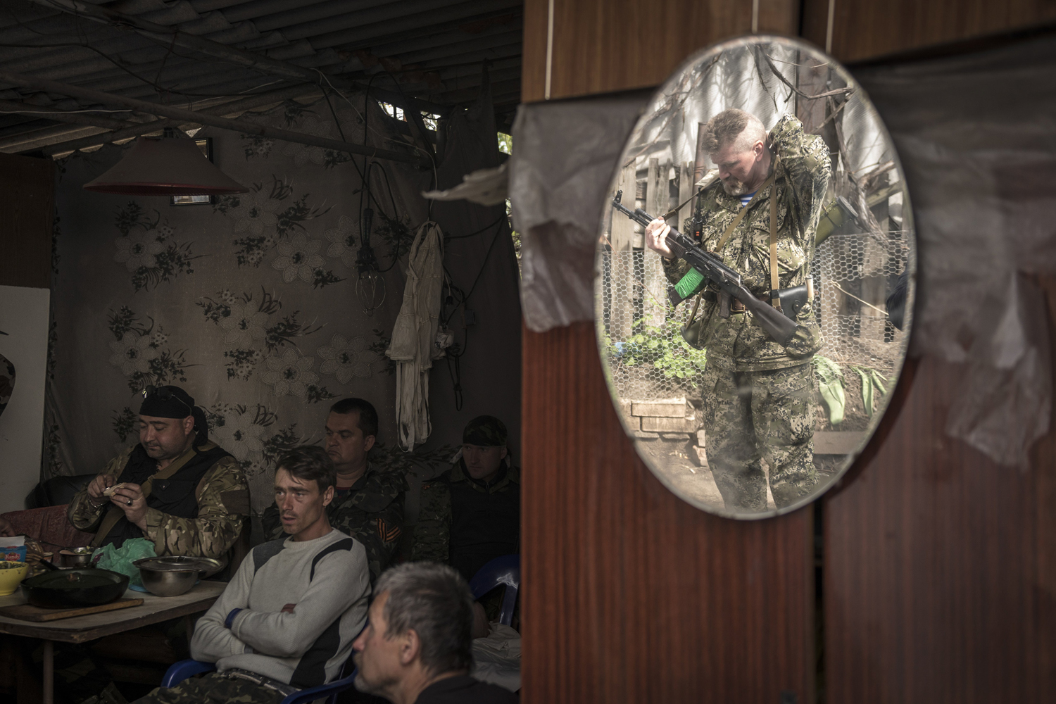 May 9, 2014. A pro-Russian militant is reflected in a mirror as he adjusts his rifle, while others watch a Victory Day military parade in Moscow on the television.