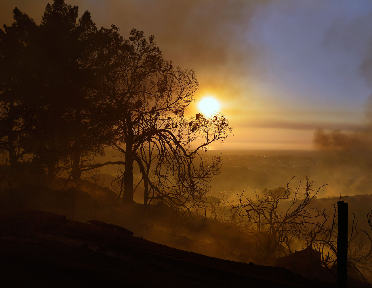 Smoldering trees obscure the sunset atop a hill in San Marcos, San Diego county, Calif., May 14,  2014.