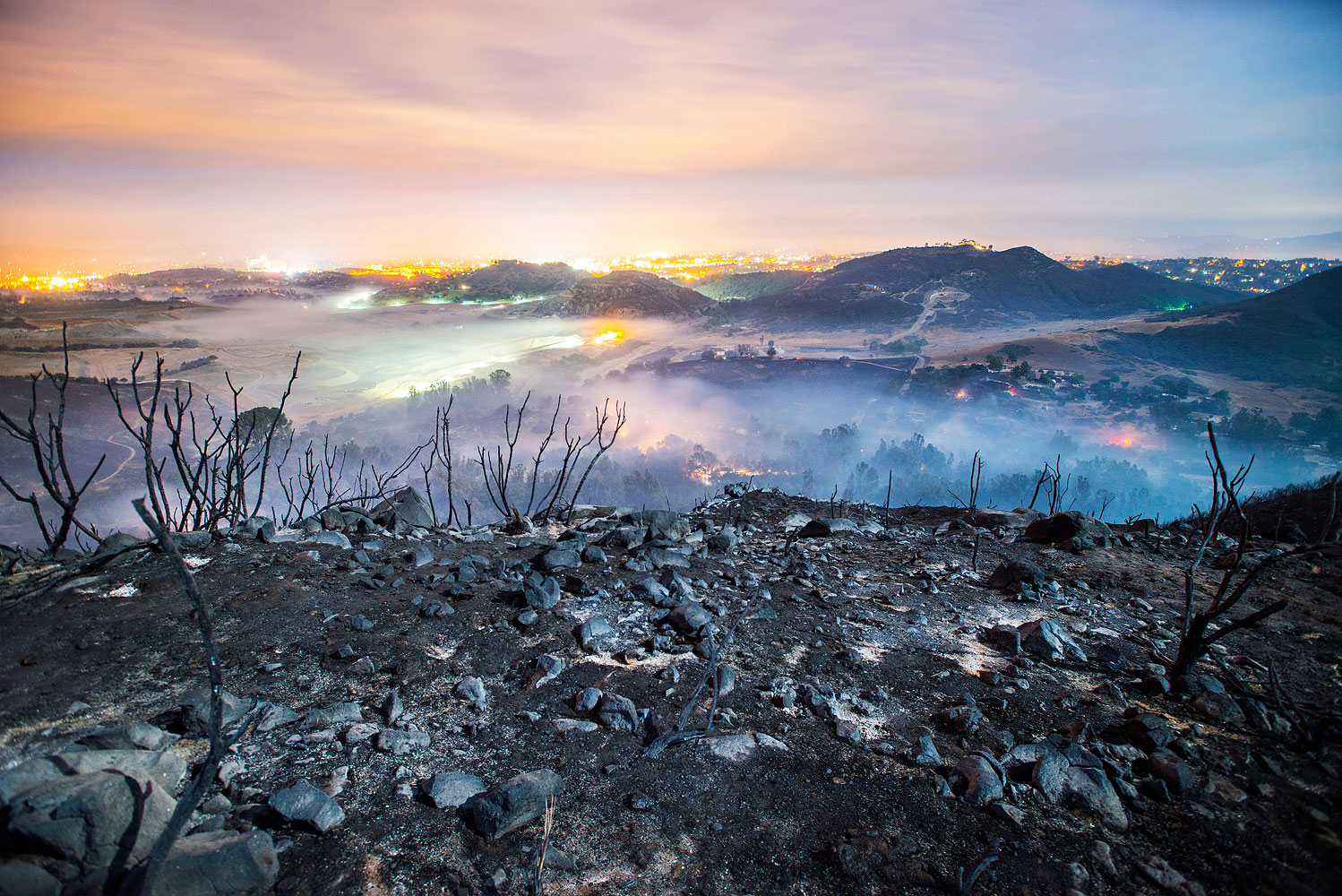 A longtime exposure shows smoldering remains of overnight fires on the hillsides of San Marcos, San Diego county, Calif., May 16, 2014.