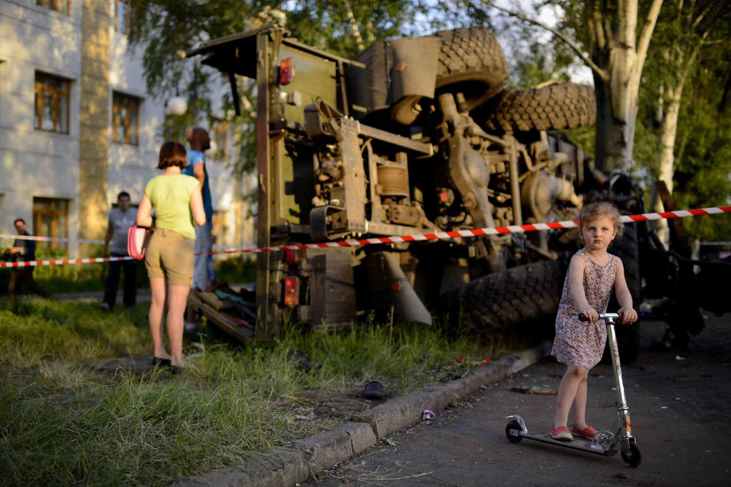 May 28, 2014. A  Ukrainian girl playing near the wrecked truck of supporters of the self-proclaimed 'Donetsk People's Republic' in Donetsk, Ukraine.