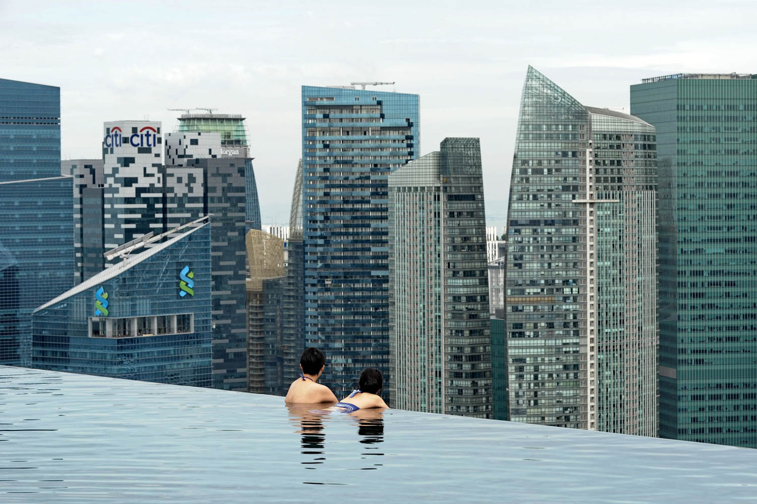May 20, 2014. Visitors look at a view of the city skyline from the rooftop pool of the Marina Bay Sands resort hotel in Singapore.
