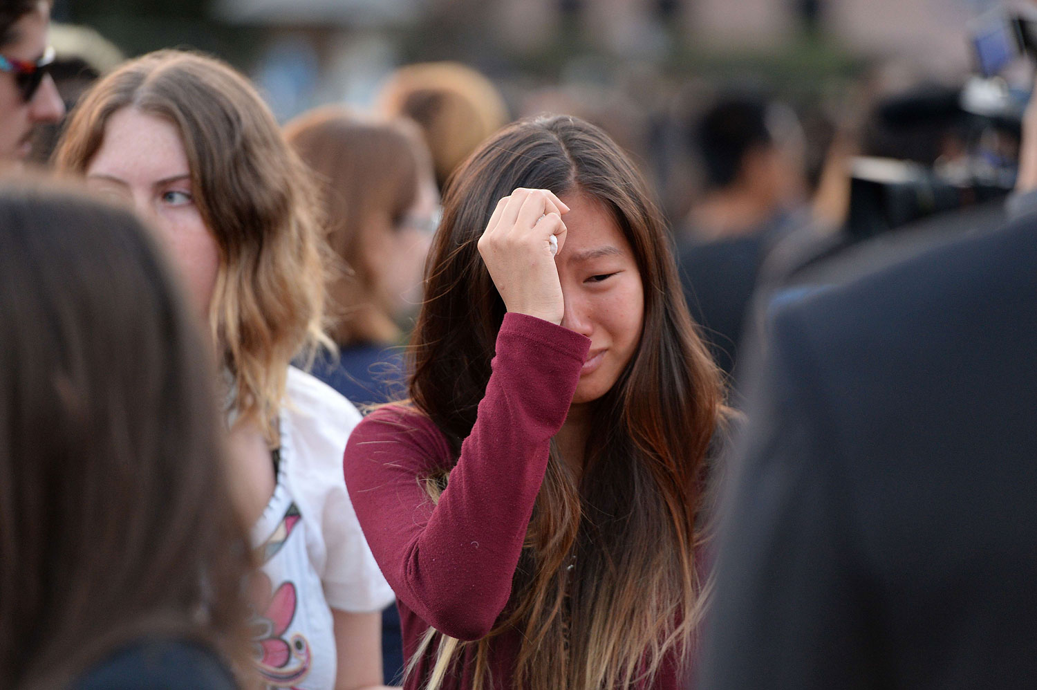A student weeps during a candlelight vigil on May 24, 2014, for those affected by a killing spree in Isla Vista, on the University of California, Santa Barbara, campus