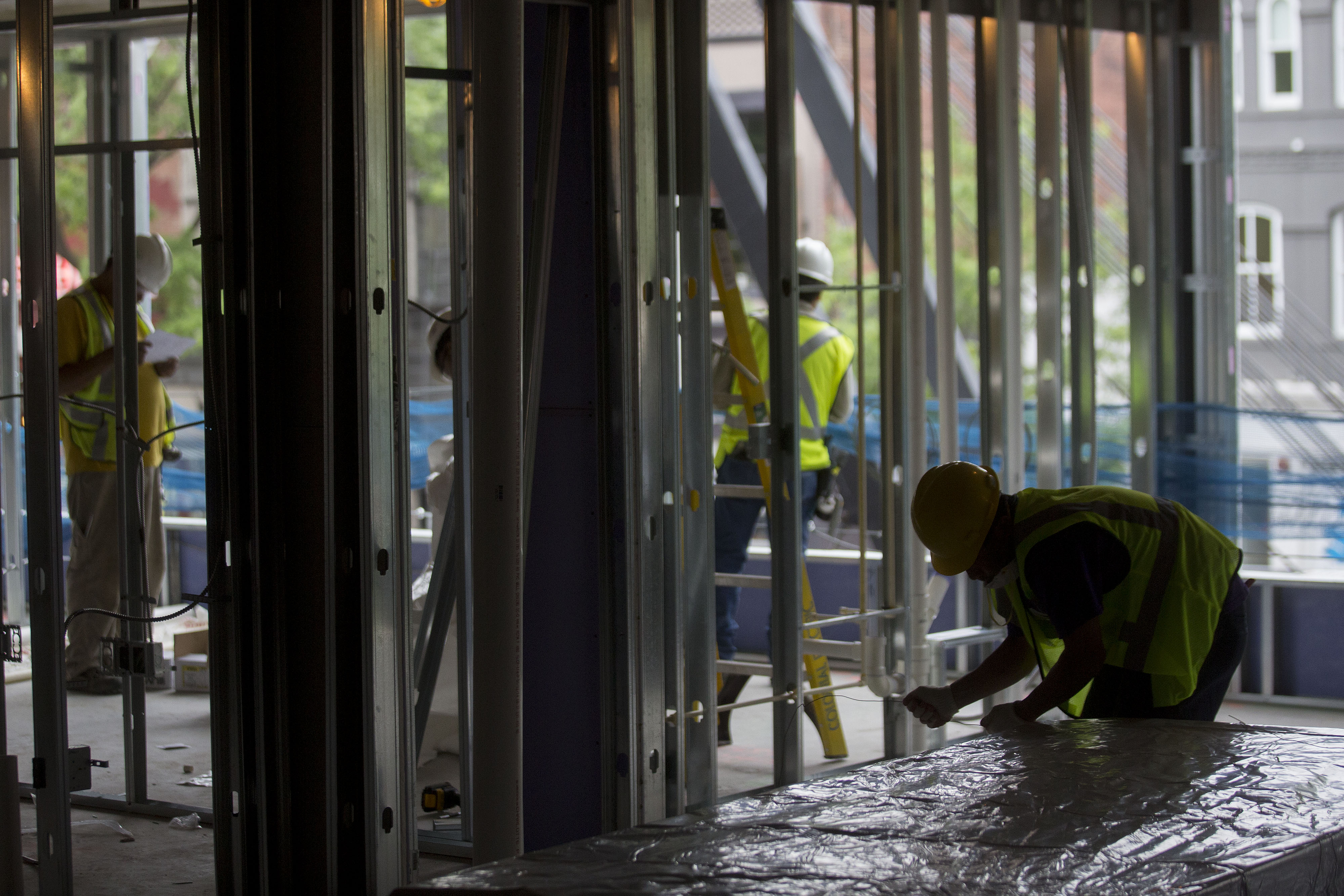 Subcontractors work at the Donohoe Construction Co. Bentley retail and apartment building under construction in Washington on May 14, 2014.