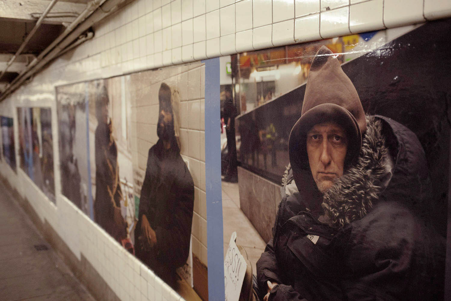 Artist Andres Serrano's photographic installation, Residents of New York, at the West 4th Street subway  station in New York City.
