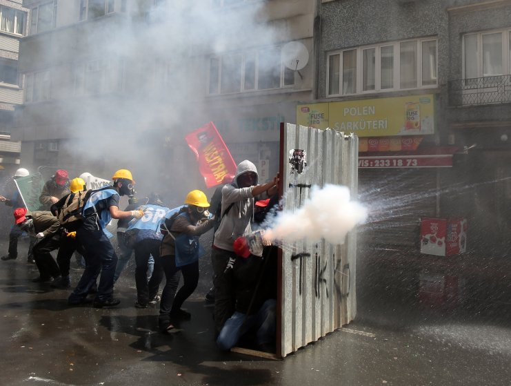 Protesters fire back as riot police use water cannons and teargas to disperse thousands of people trying to reach the city's main Taksim Square to celebrate May Day in Istanbul, May 1, 2014.