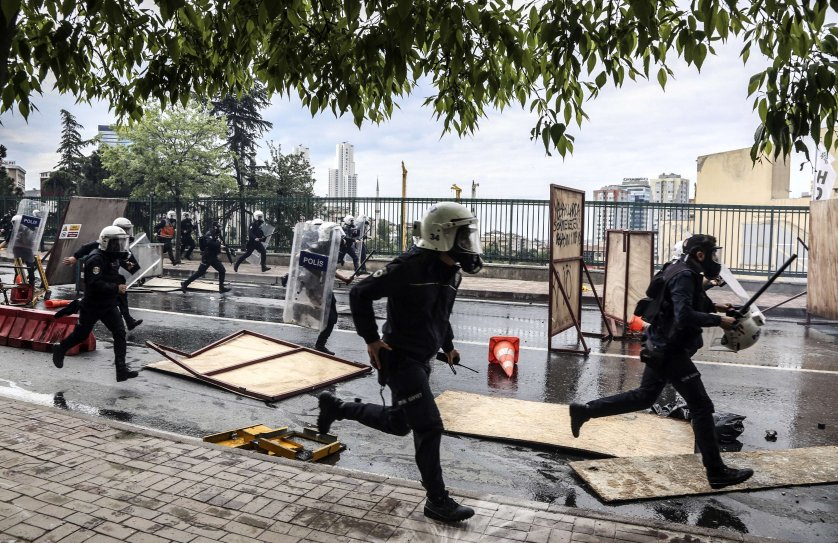 Turkish riot policemen run after protesters to disperse a May Day rally near Taksim Square in Istanbul on May 1, 2014.