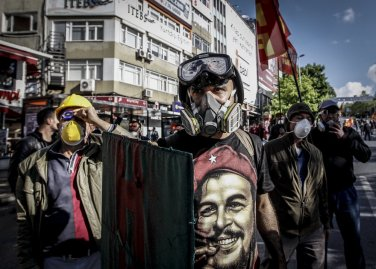 A Turkish protestor wearing a gas mask and a hard hat takes cover during clashes with riot police who prevent demonstrators from reaching Taksim Square in Istanbul for a May Day rally on May 1, 2014.